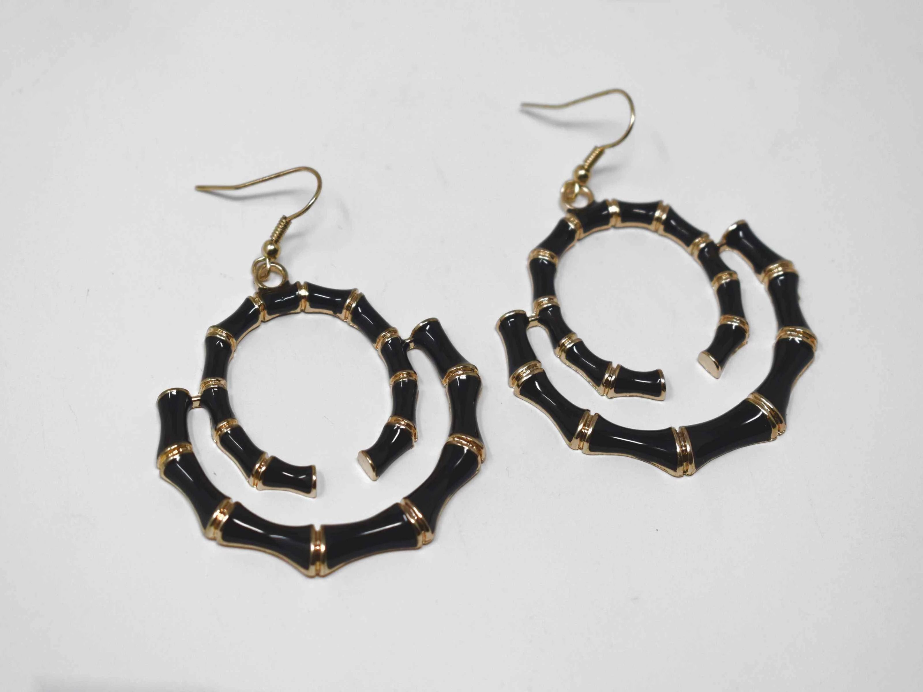 "Our Bombays carved bamboo style earrings with a fish hook clasp is gold in tone and black in color. It has a swirled bamboo design measuring 2 1/2"" inches in length.   Gold tone unique bamboo print 2 1/2"" in length"