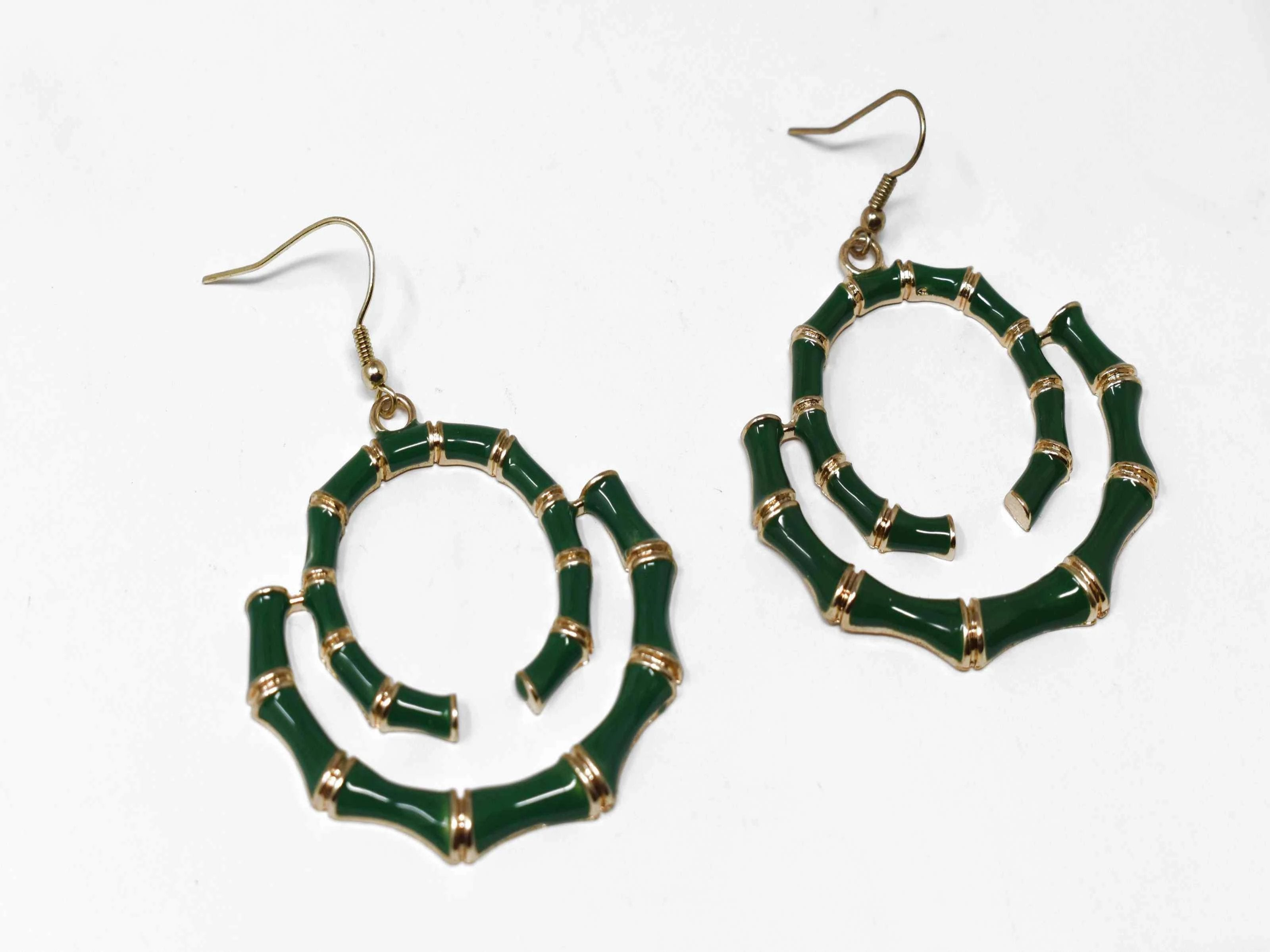 "Our Bombays carved bamboo style earrings with a fish hook clasp is gold in tone and green in color. It has a swirled bamboo design measuring 2 1/2"" inches in length."