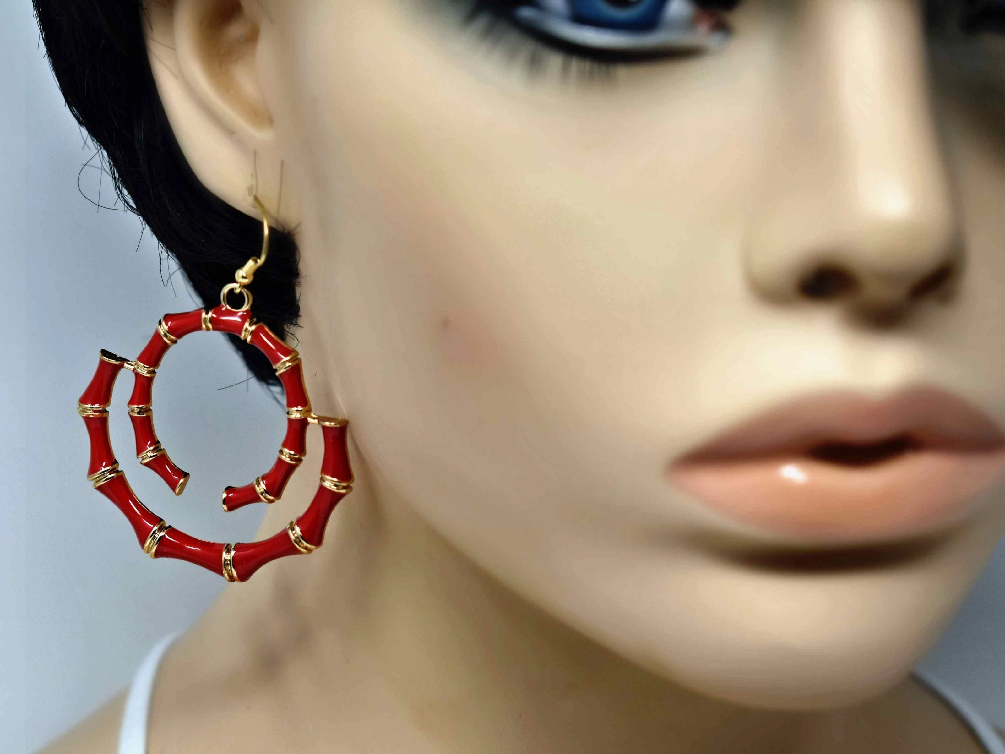 "Our Bombays carved bamboo style earrings with a fish hook clasp is gold in tone and red in color. It has a swirled bamboo design measuring 2 1/2"" inches in length.   Gold tone unique bamboo print 2 1/2"" in length"