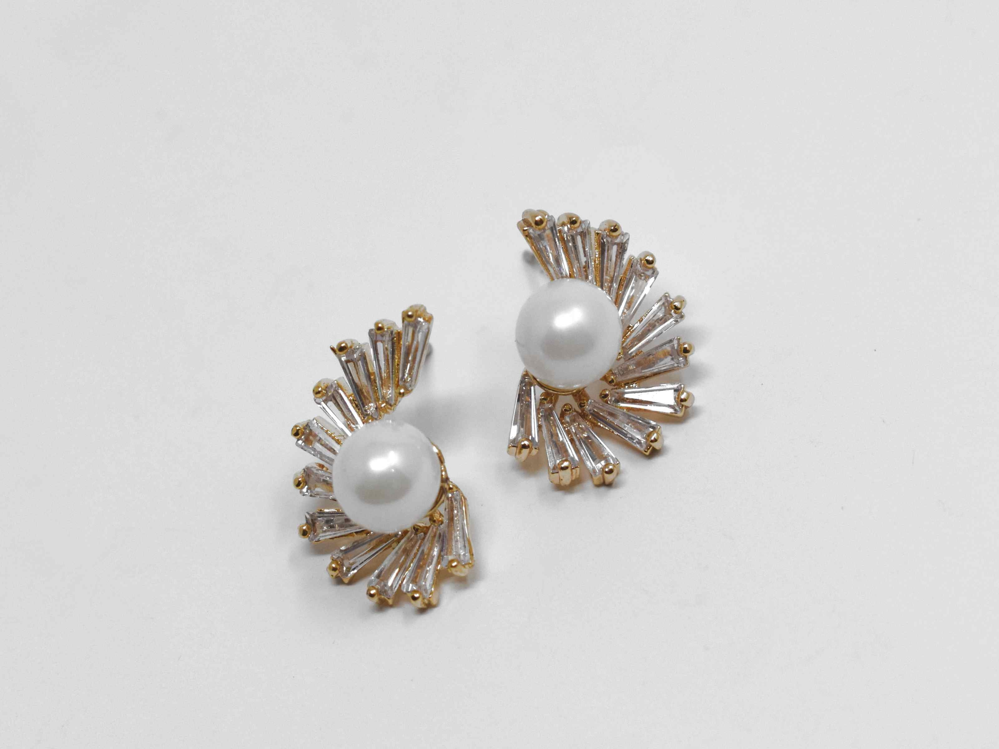 Our bouvardia earrings are a beautiful classic with a modern twist. These knob earrings have a pearl core adorned with cascading stones. They are 3/4 of an inch in length with a push back clasp.