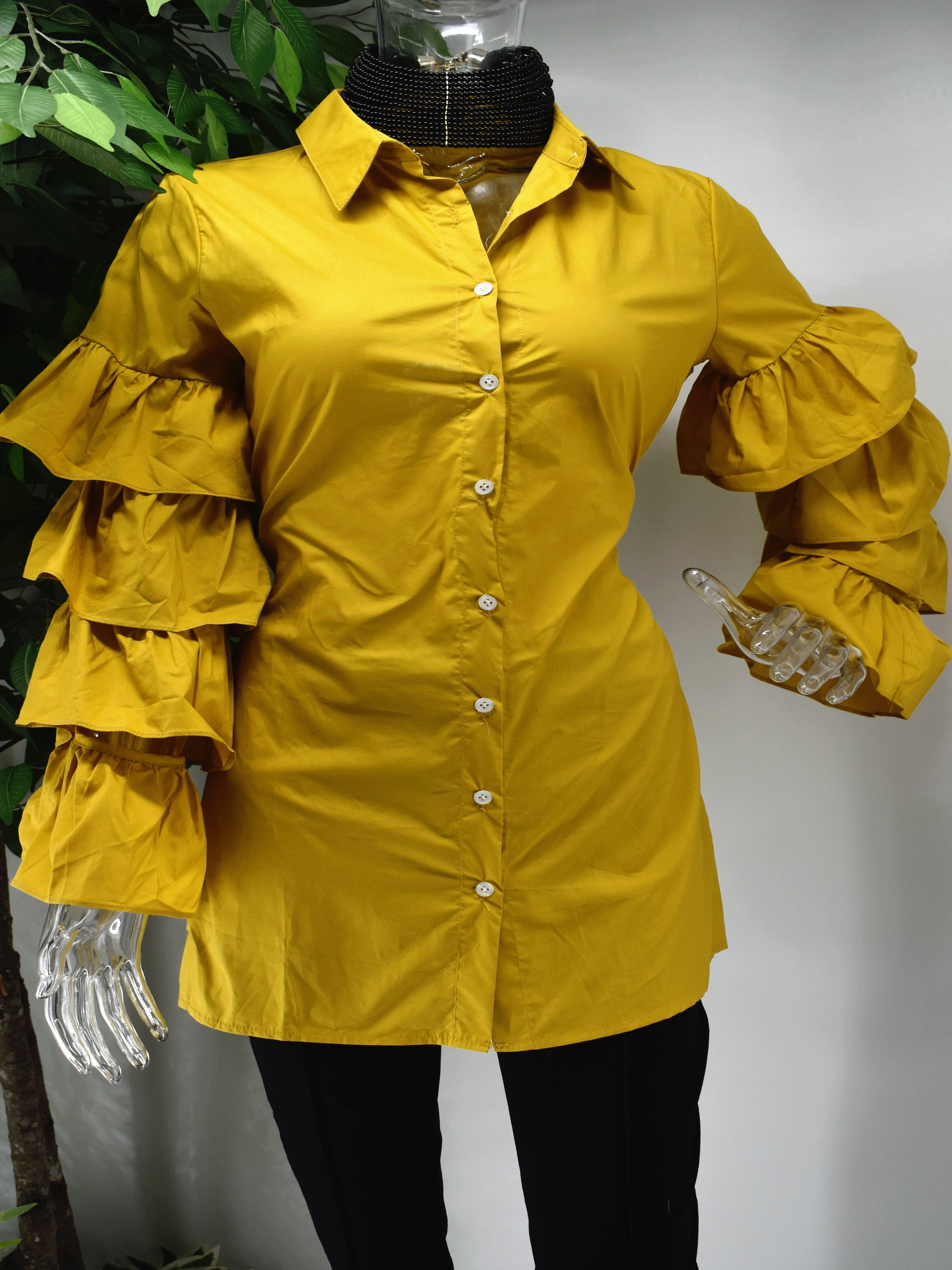 Turn heads and represent how fashionably fierce you are in our Brandis Mustard ruffle sleeve shirt top.  Our Brandis is a long button front shirt top with a traditional collar and a romantic bold four tiered ruffle sleeve.