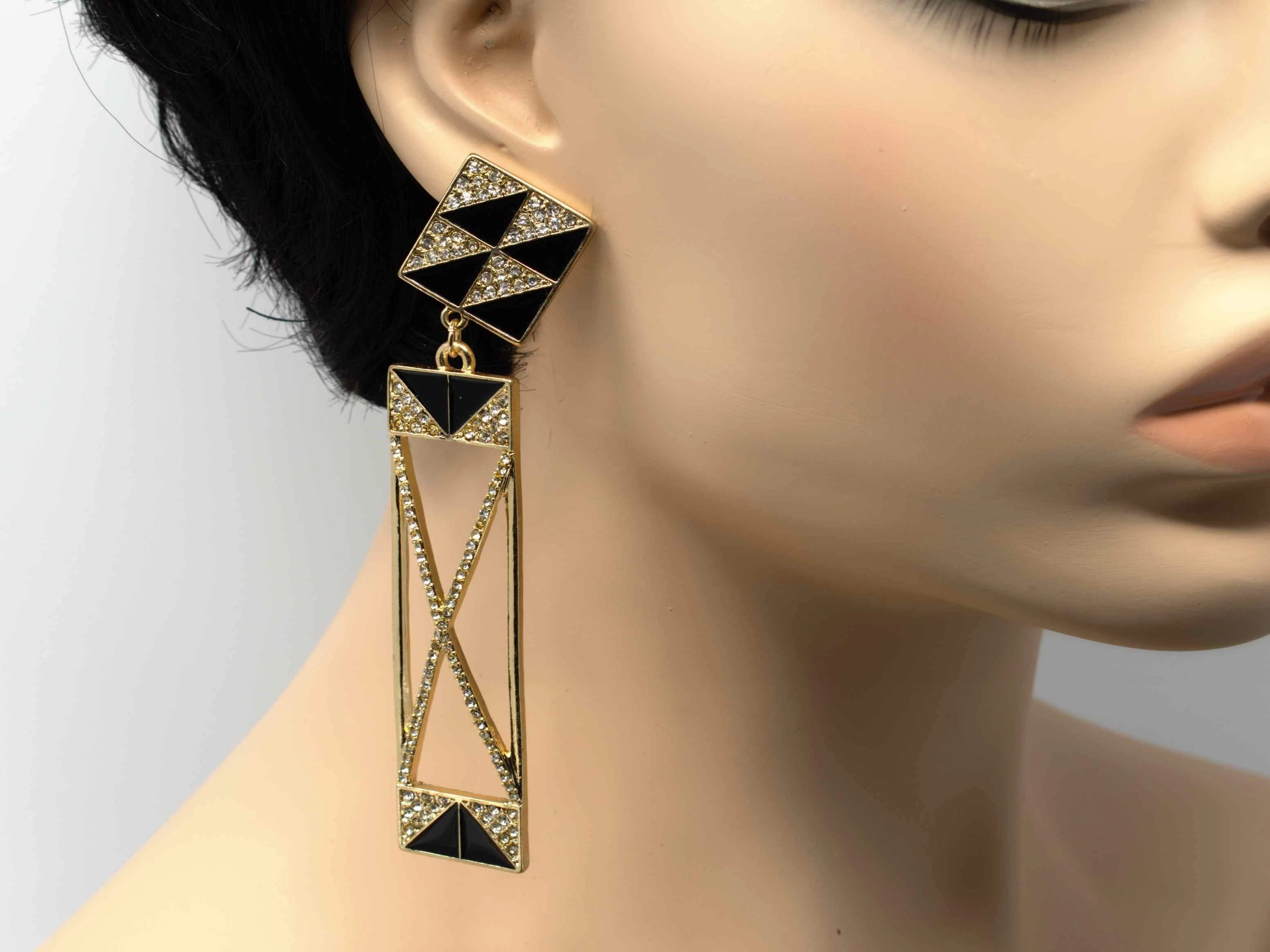A gold dangle drop chandelier earring with stone accents and a push back clasp.
