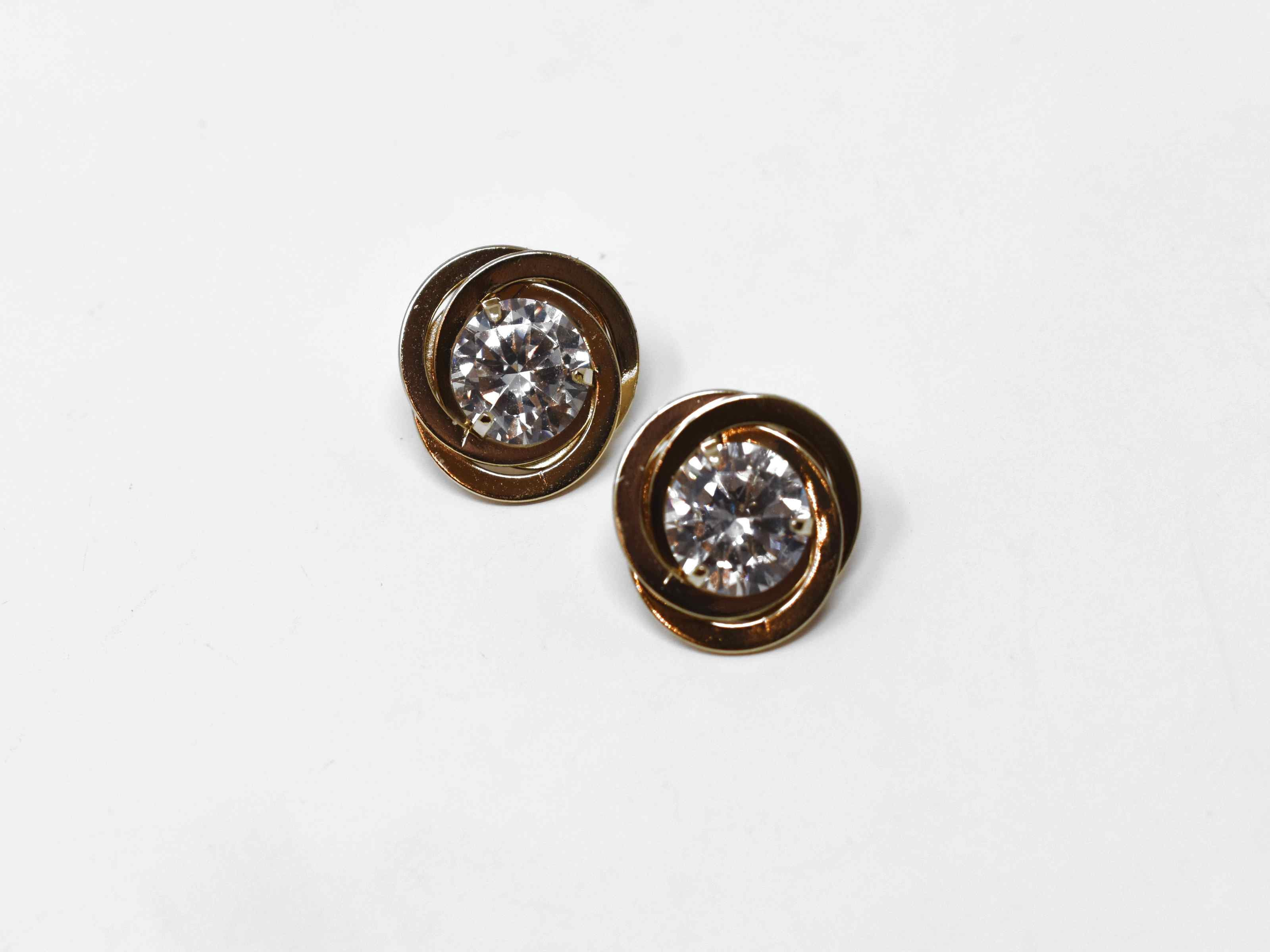 Our Buttercup gold earrings makes a cute statement for every occasions. They have three rings linked together centered by a clear stone. It has a push back clasp and a 1/2 inch in length.