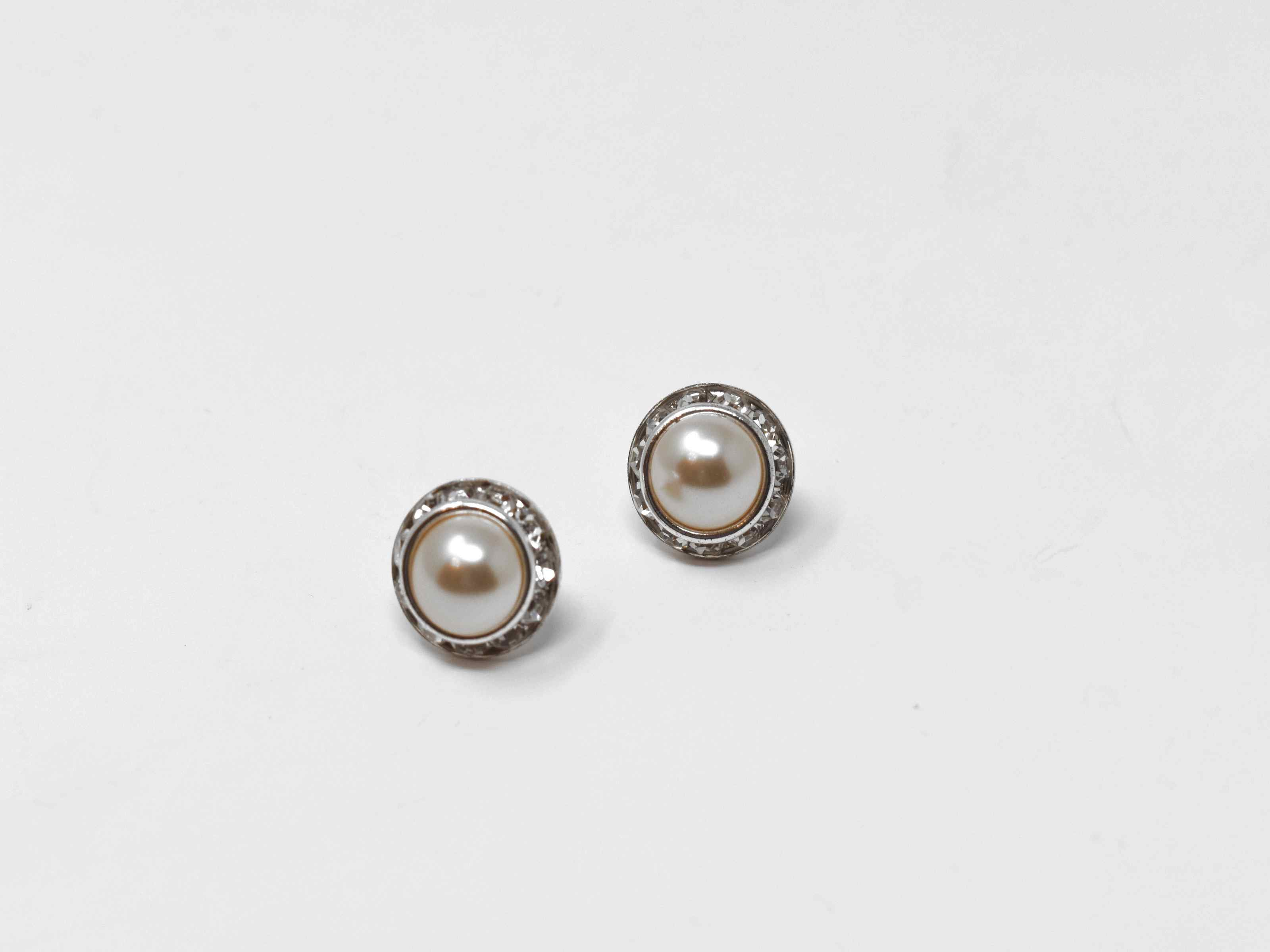 We would love for you to enjoy our delicate but chic calendula pearl knob earrings. These earrings have a champagne center pearl surrounded by a halo of stones. They are a 1/2 inch in length with a push back clasp.