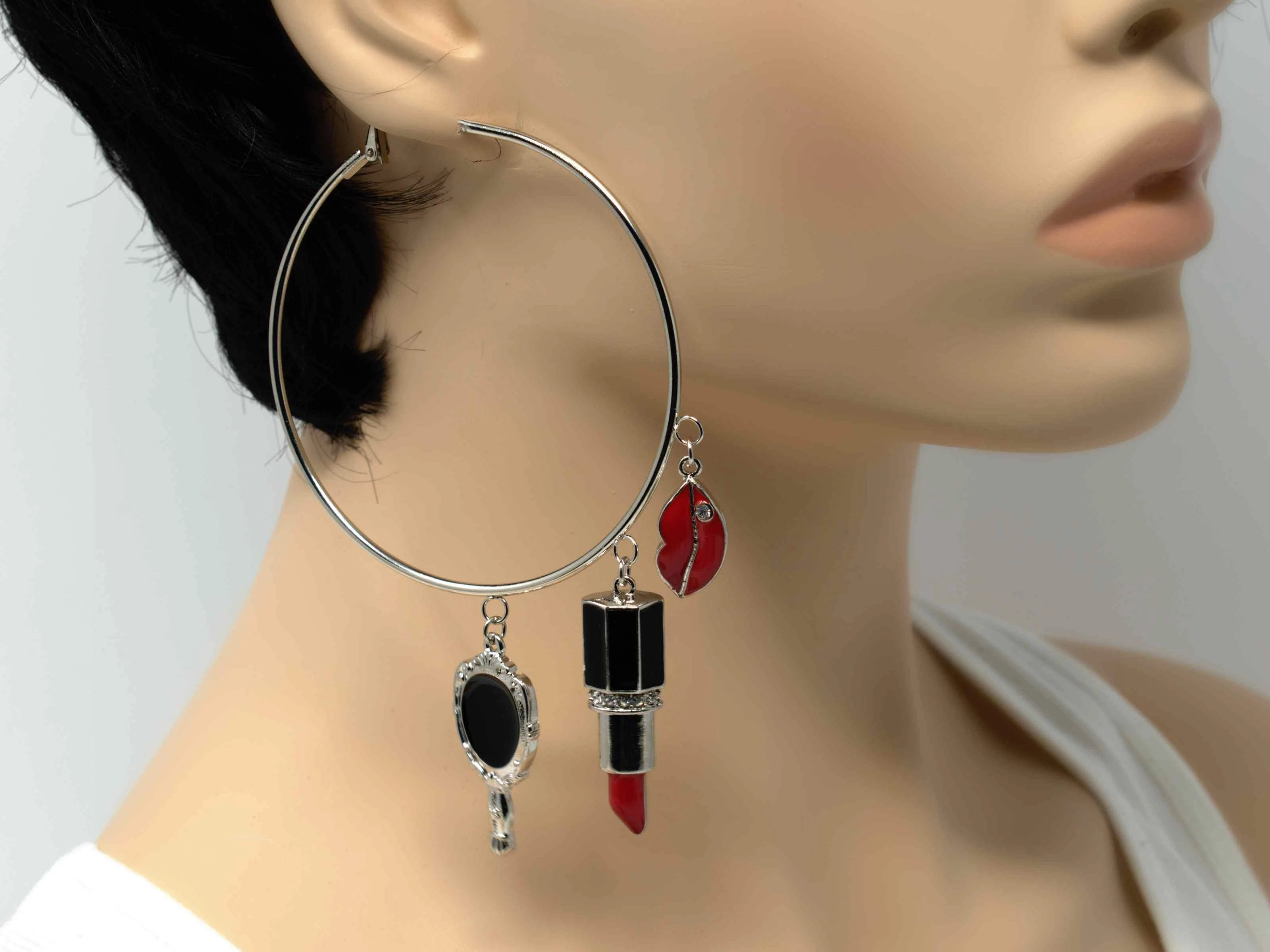 An eye-catching silver hoop earring with makeup charms.