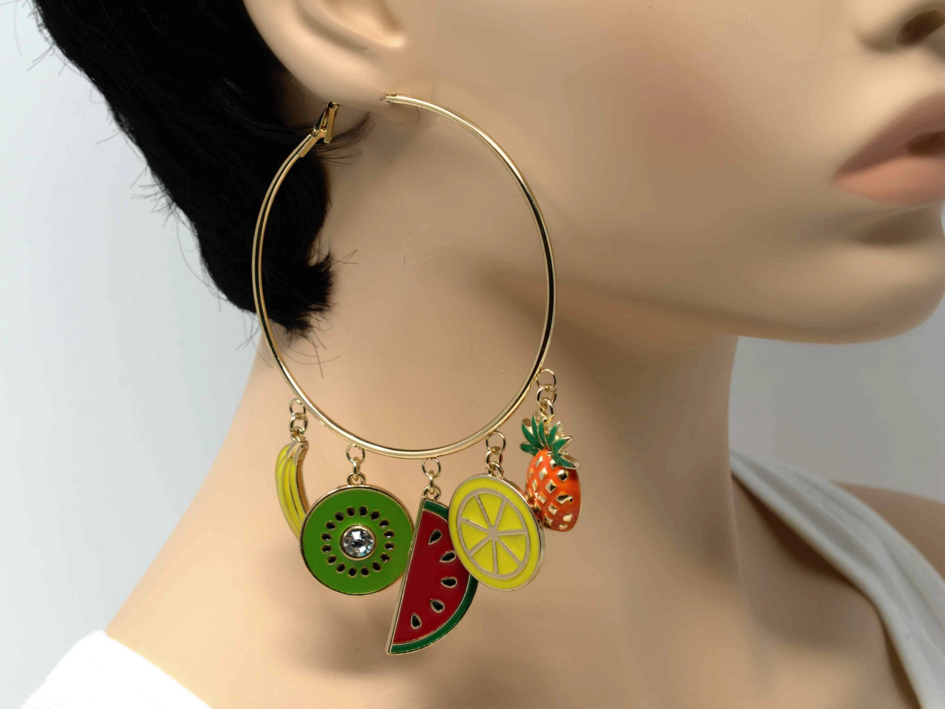 An exotic gold hoop fashion earring with tropical fruit charms.