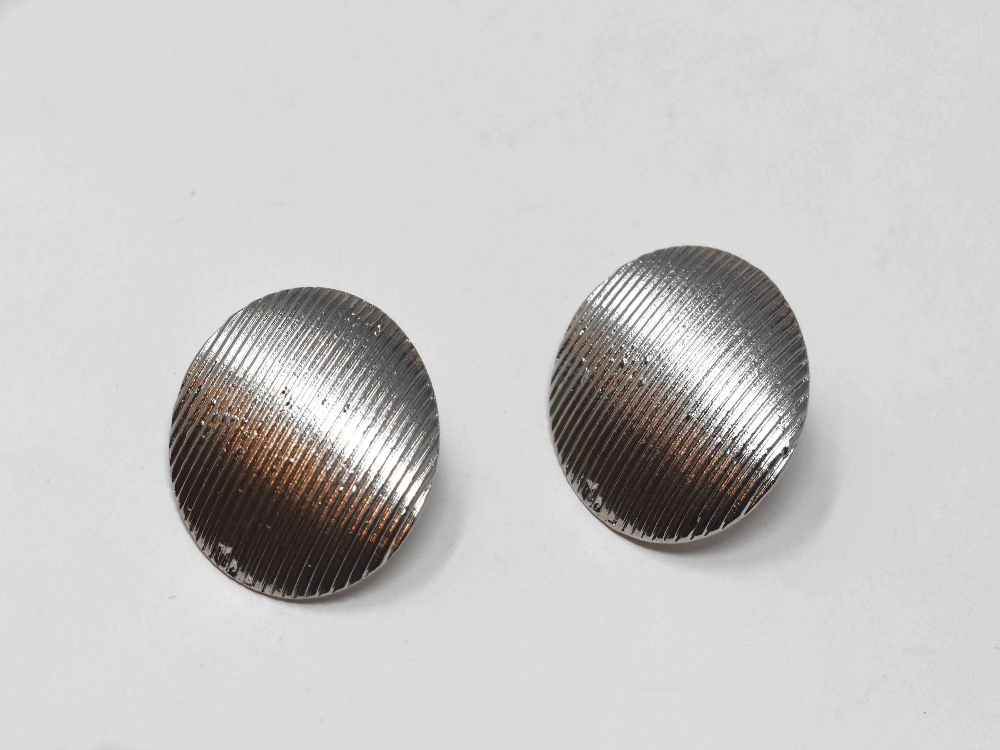 Our Dahli Silver earrings are good for any occasion. They are silver medium sized knob earrings with a pinstripe design and a pushback clasp.