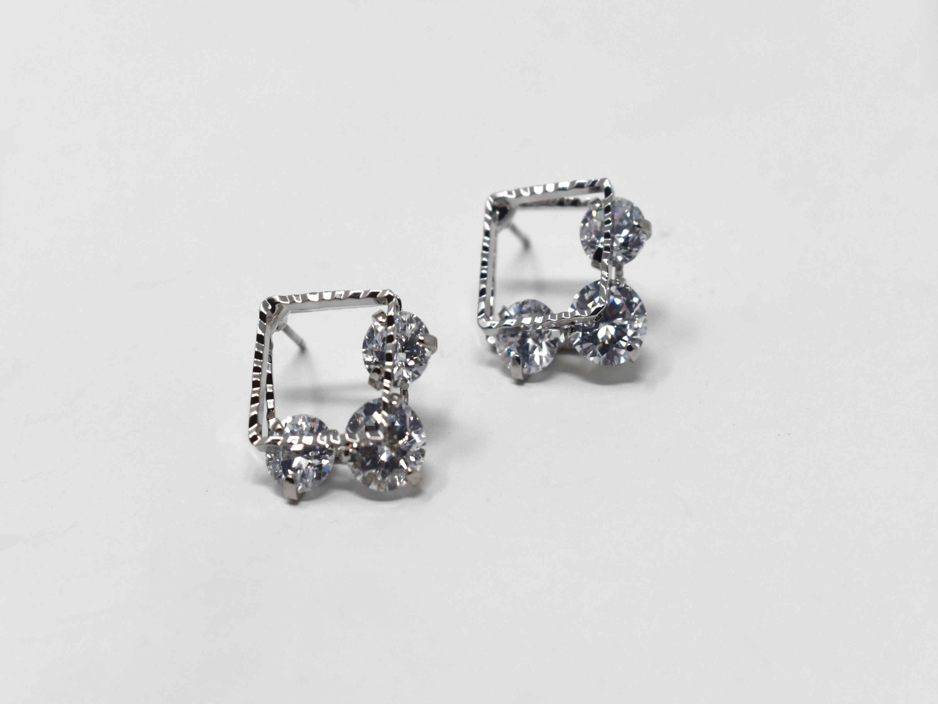 Our beautifully crafted daniella earrings are a must have essential. These silver double square earrings are adorned with stones running between both squares. It is 3/4 of an inch in length with a push back clasp.