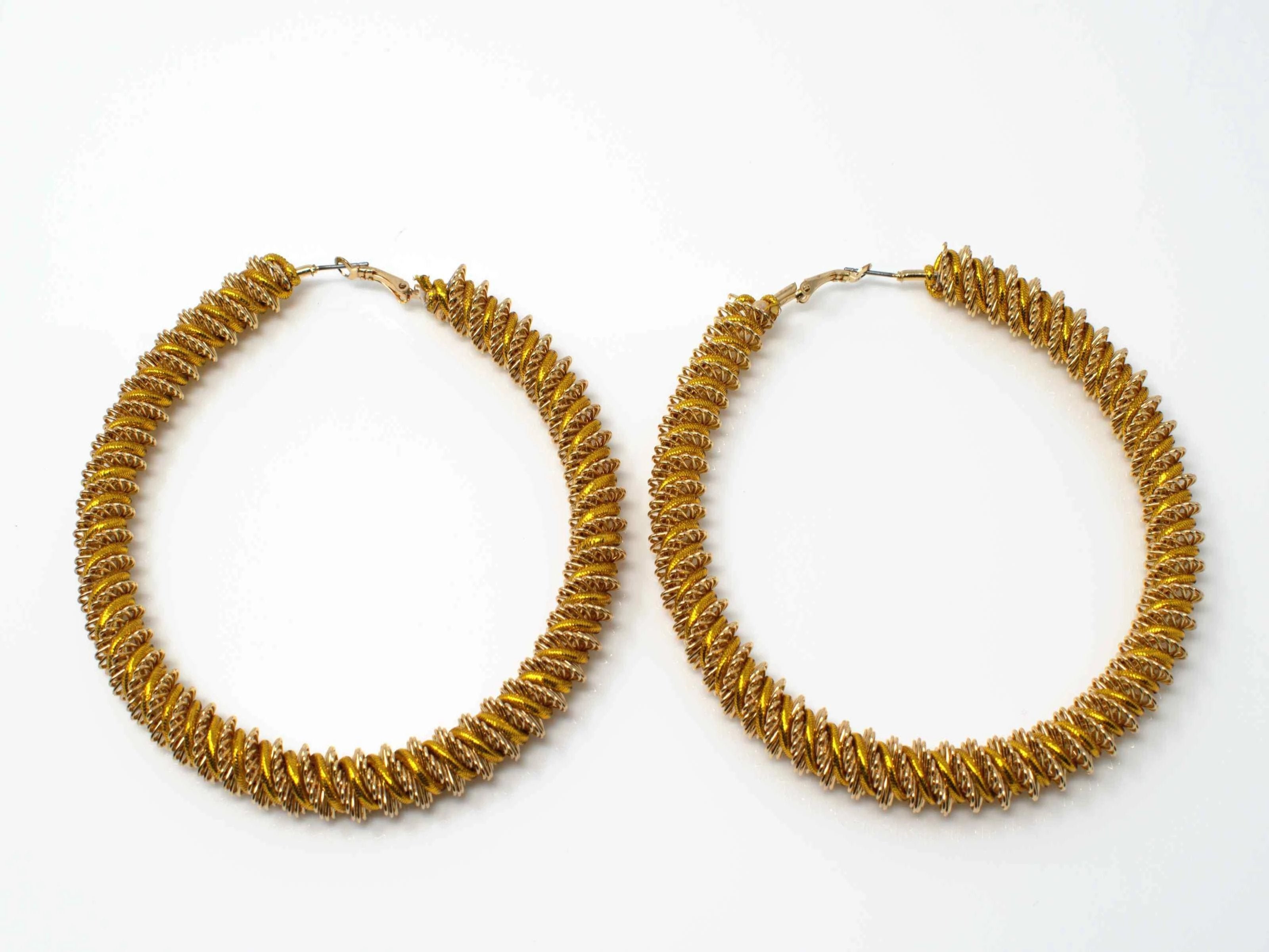 A striking stylish gold with gold trim oversized hoop with its reworked design improves on a classic.