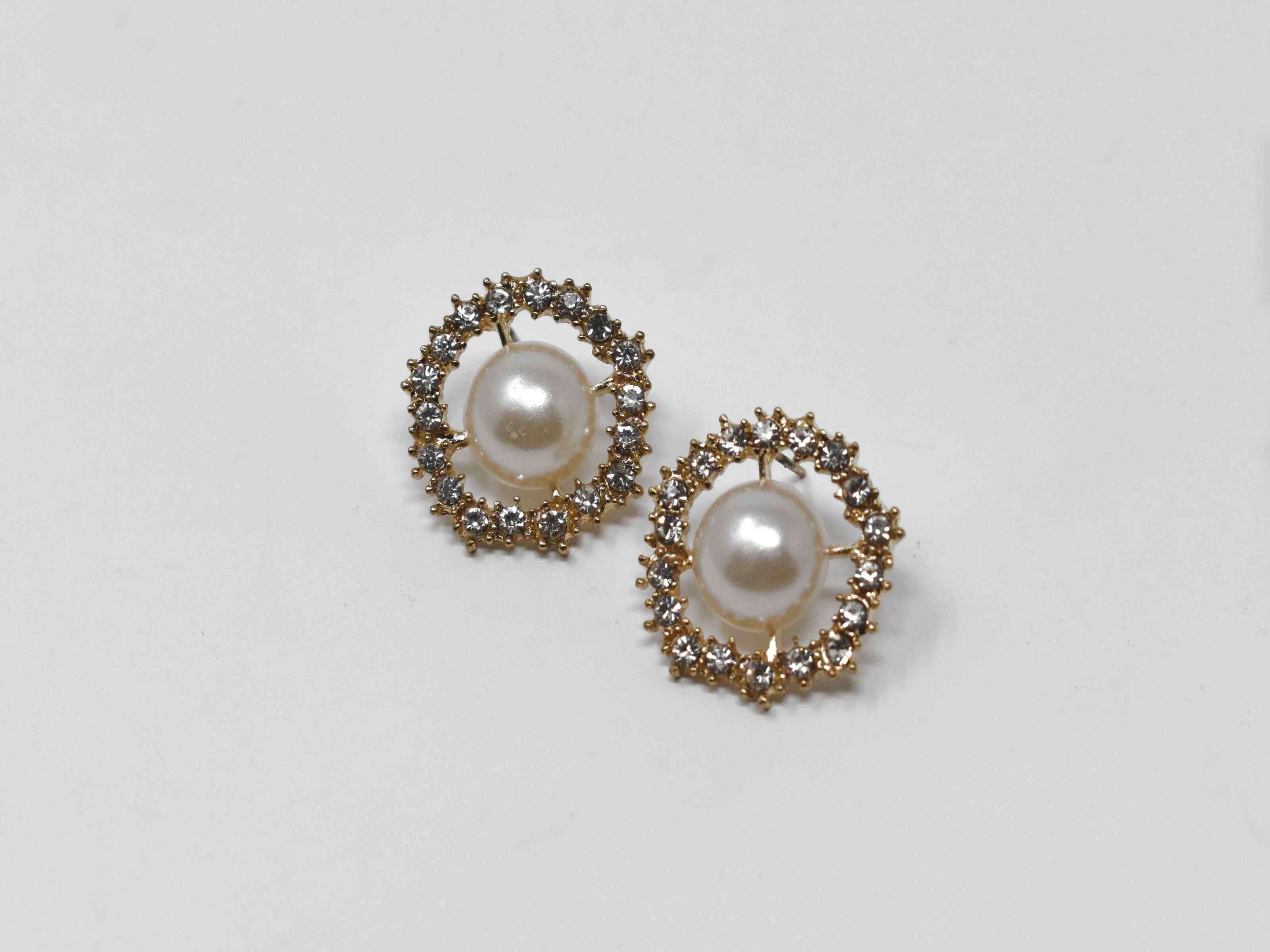Our dietes earrings are a must have staple with a burst of sparkle. These earrings are a gold tone with a pearl core surrounded by a beautiful halo of stones. They are 3/4 inches in length with a push back clasp.