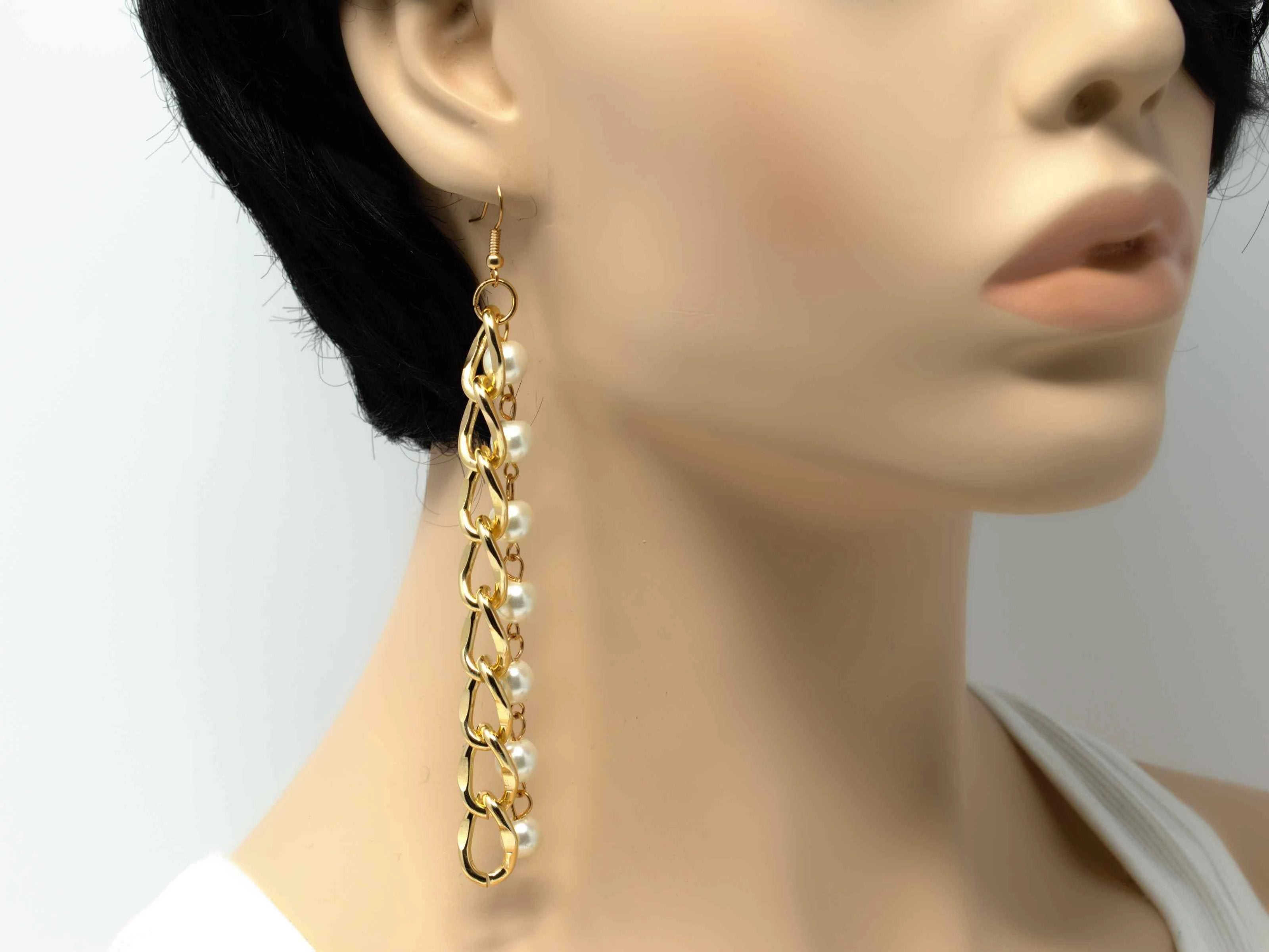 An elegant gold drop dangle earring with pearl accents and a fish hook clasp.