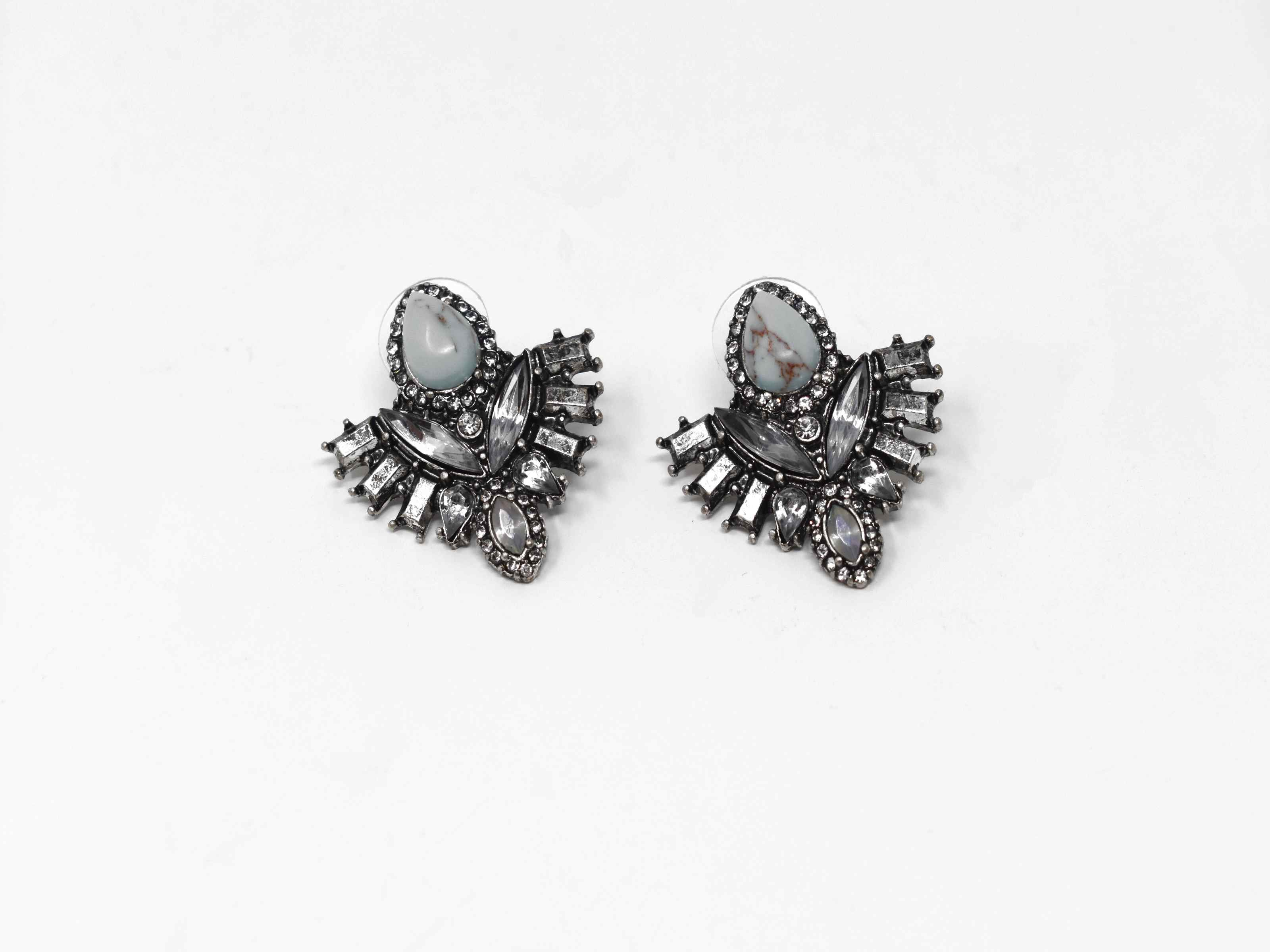 Show them who is the boss while making a statement with our Dutch iris earrings. These beauties are a antique shade of silver with iridescent stones surrounding a core turquoise stone. It has a push back clasp and measures 1 inch in length.