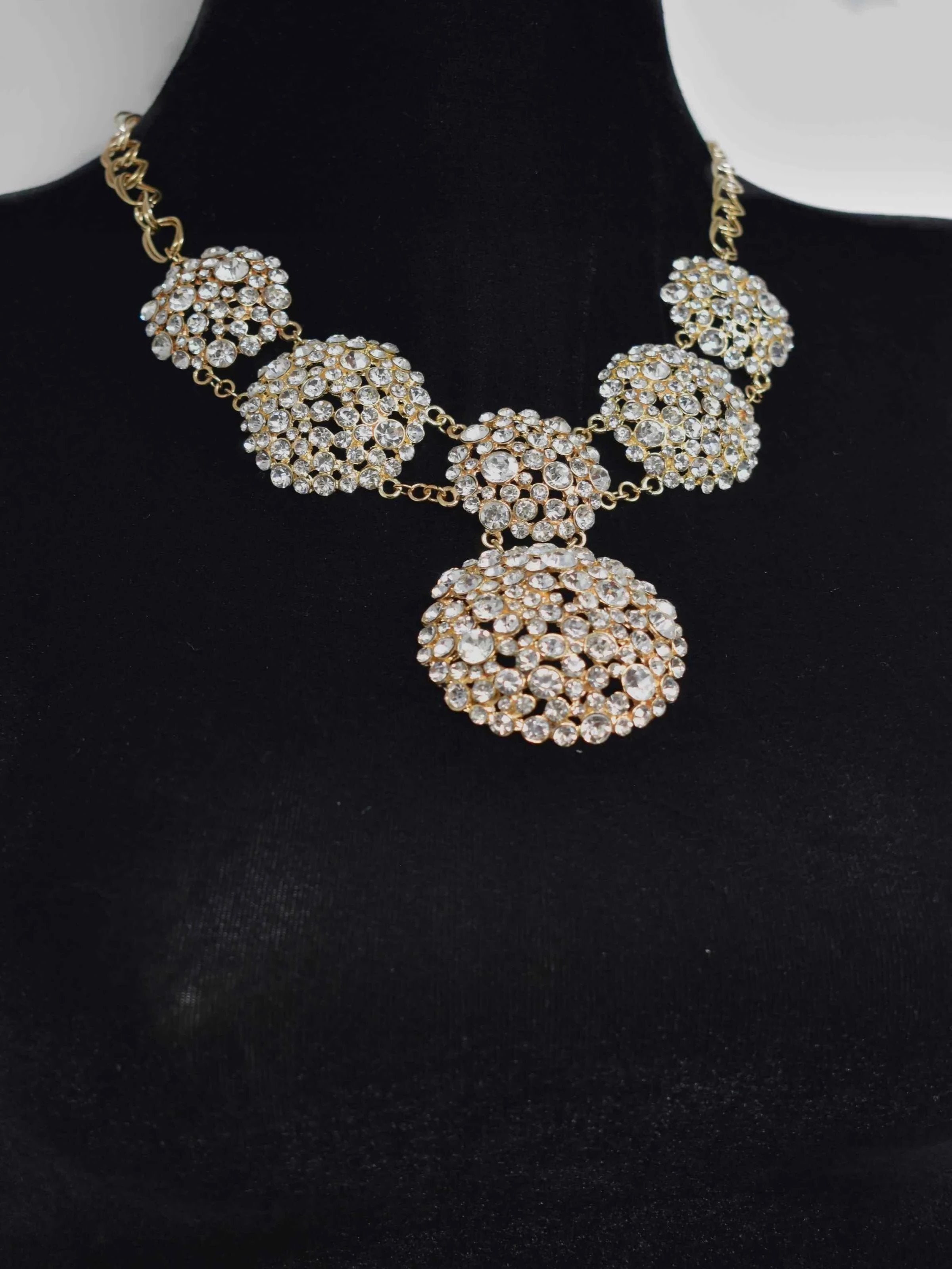 Show them how its done once you show up in our Ella statement necklace. This gold statement piece is covered in clusters of clear stones and closes off with a lobster clasp. It measures 10 1/2 inches in length.