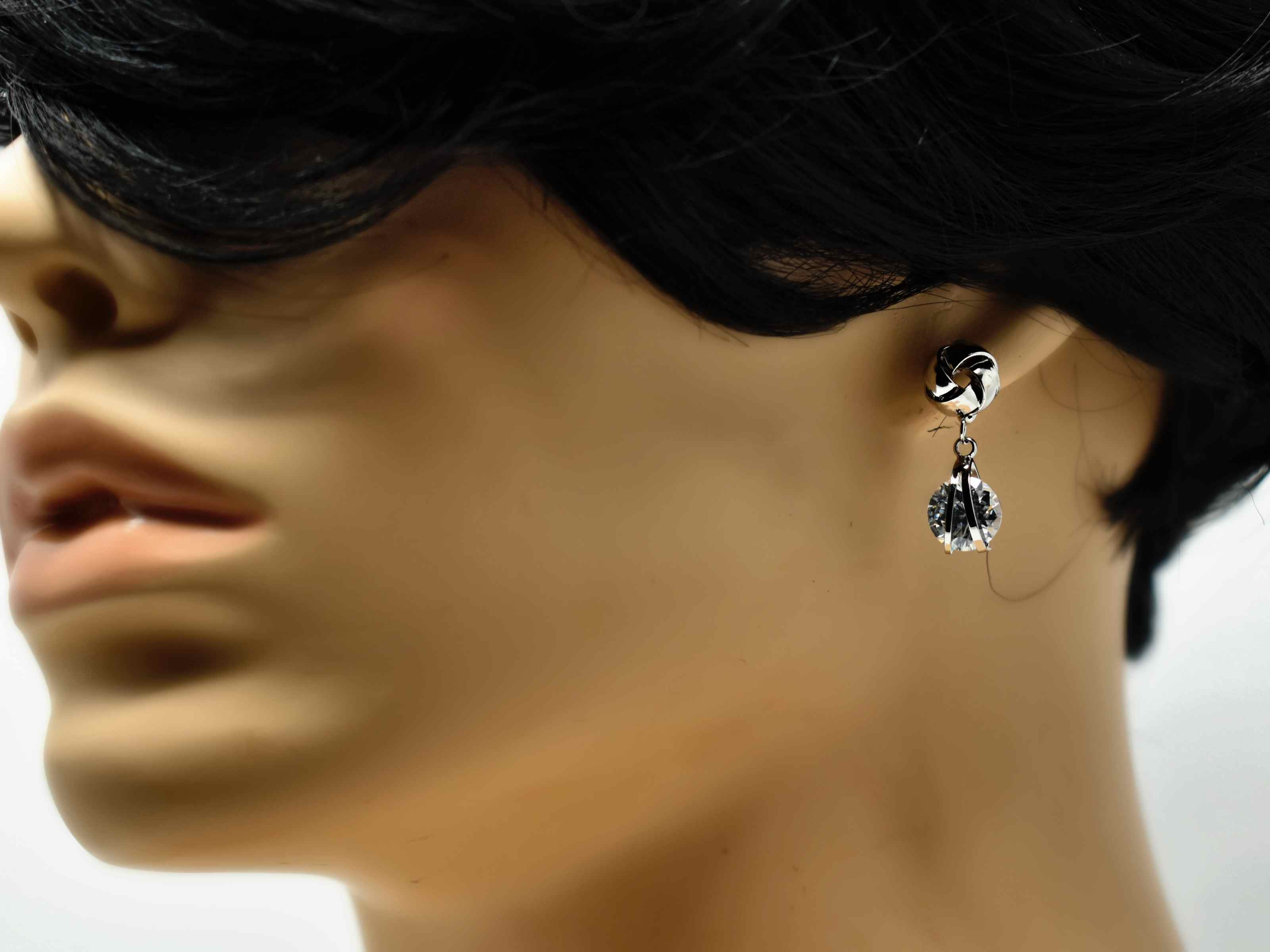 Our Erica earrings are so delicate and chic! These little silver beauties are the perfect knob chandelier earrings with a knot design and a drop dangle stone. It has a push back clasp and is 1 inch in length.