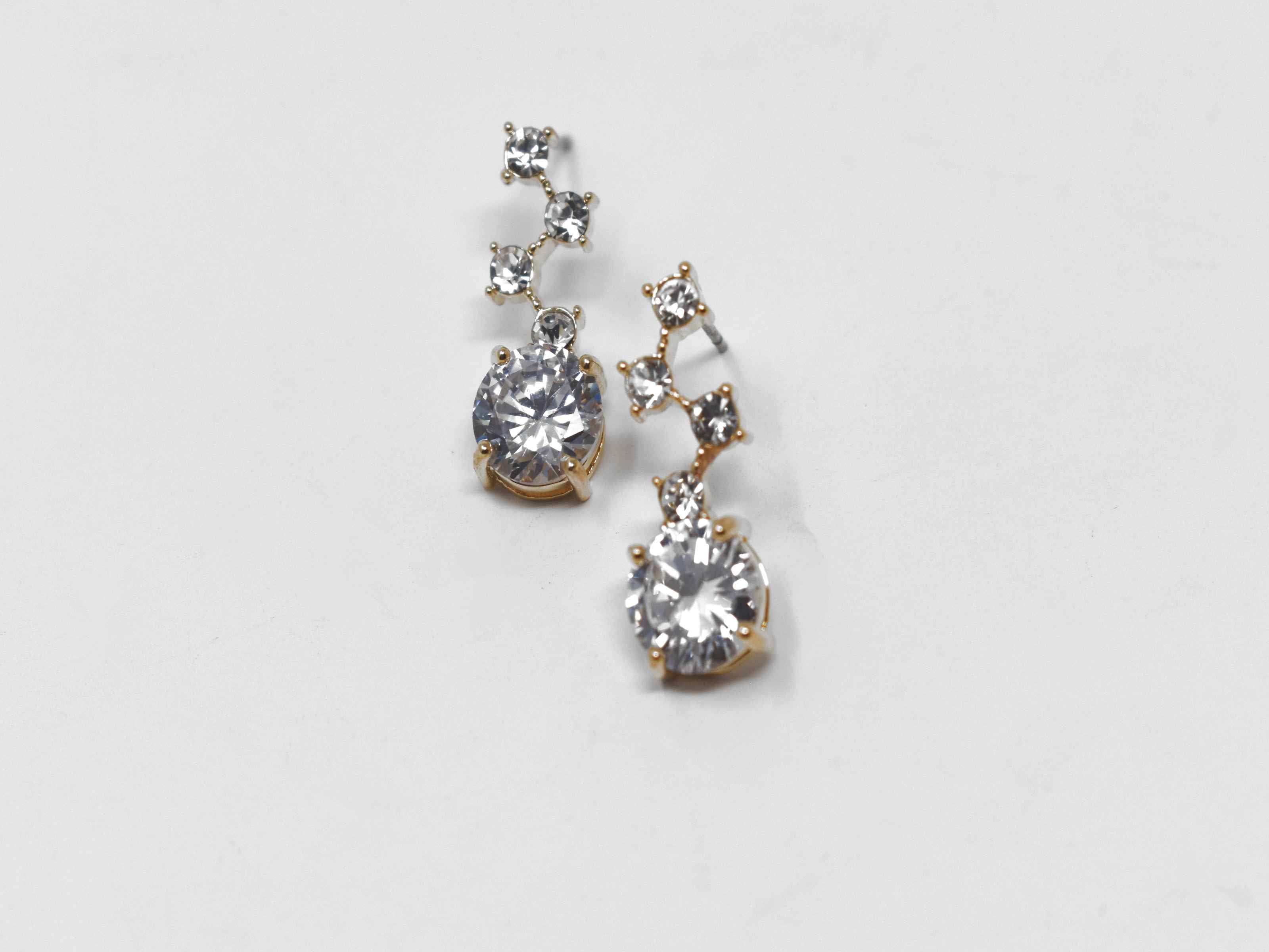Our Flannel earrings are a must have! These gold earrings are a dangly knob connected with stones. It is 3/4 of an inch in length with a push back clasp.
