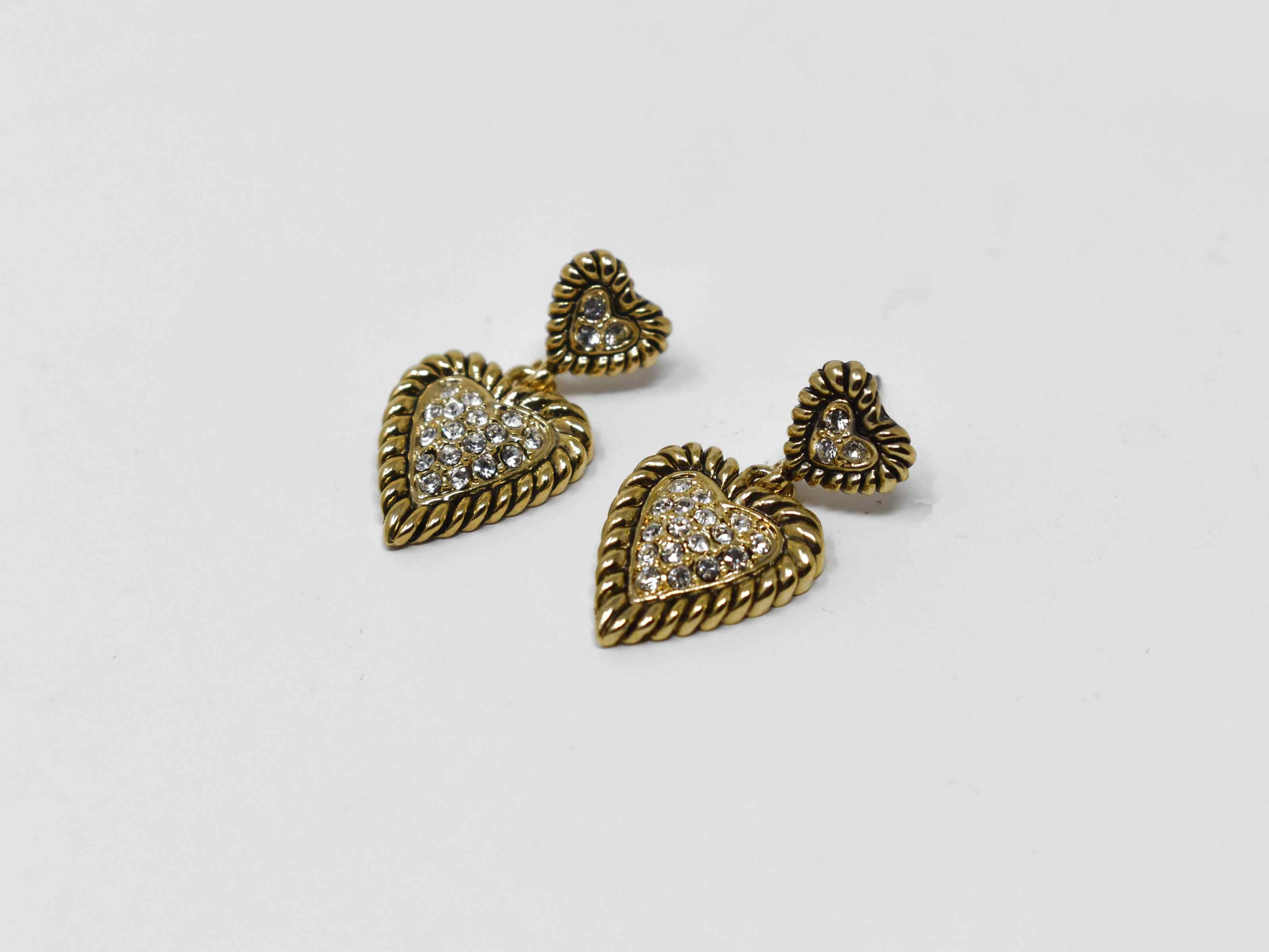 Forsythia is such a cute must have! These heart shaped designs are a gold tone adorned with stones. These earrings are 1 inch in length with a pushback clasp.