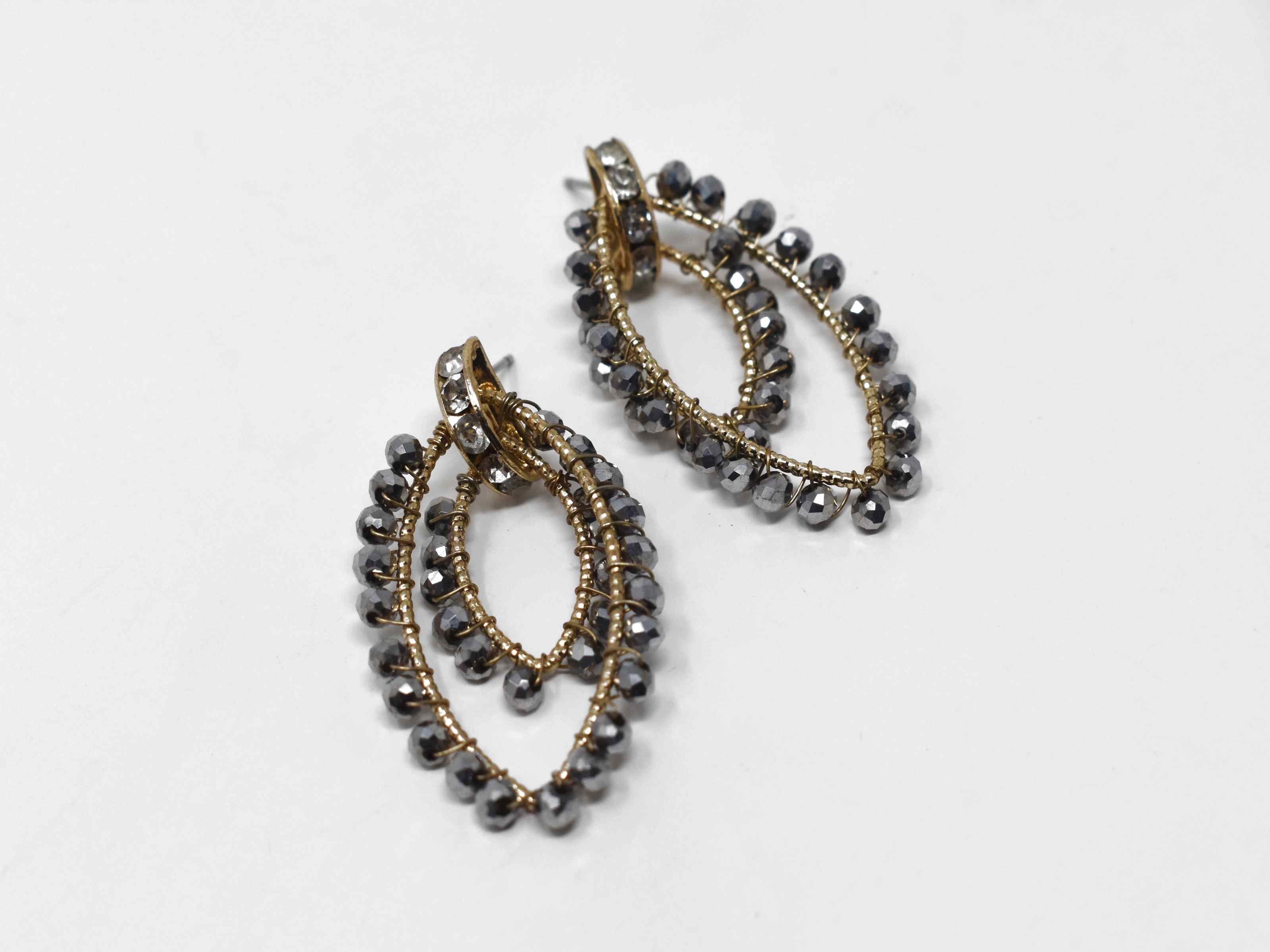 Do you want to see a new modern style with a classic twist. Come on over and take a look at our foxglove drop dangle earrings. These earrings have a gold and pewter design with a string of set clear stones. They are 1 1/2 in length with a pushback clasp.