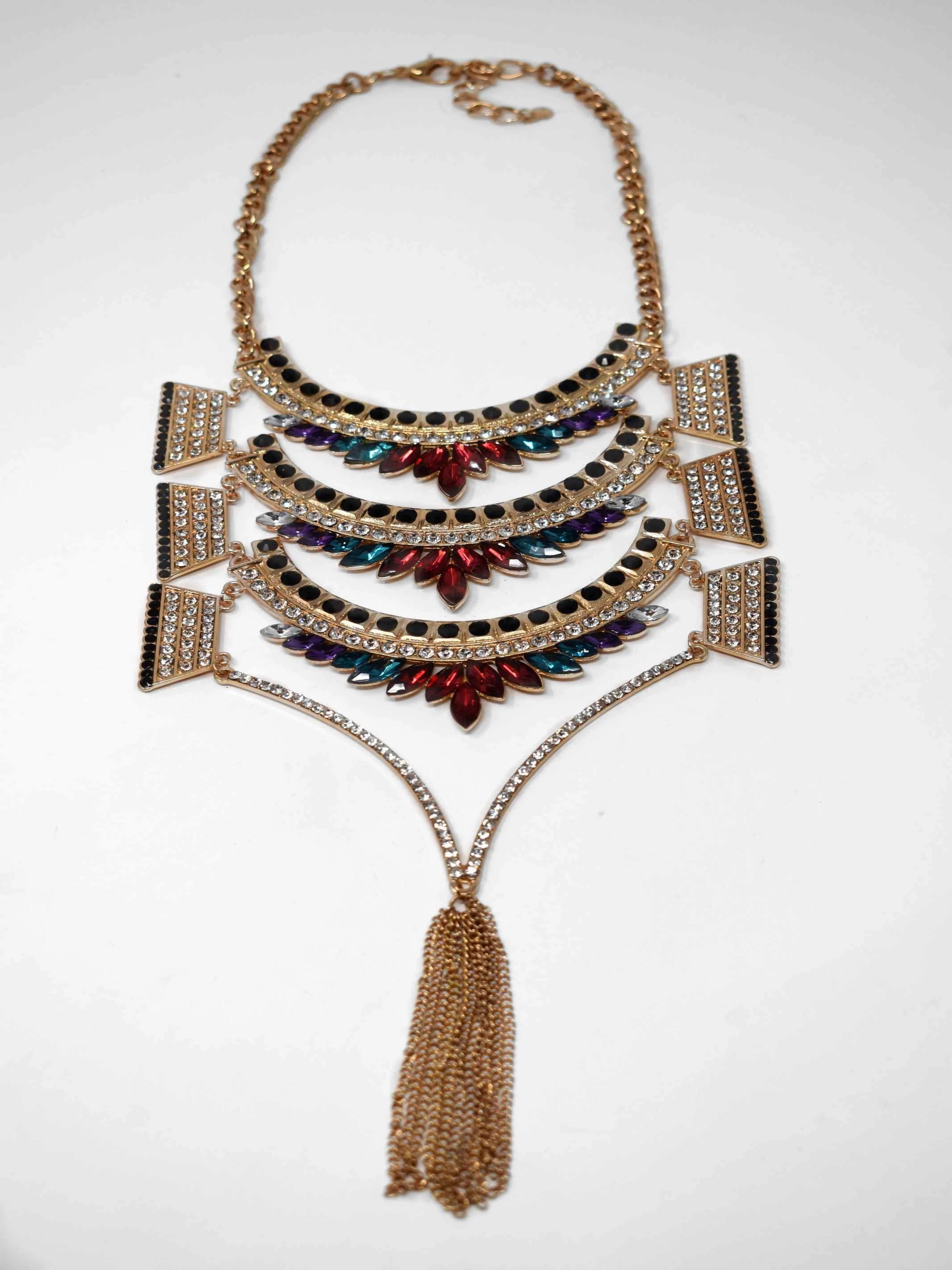 "Dare to dazzle with our Greta statement necklace. This Gold necklace is a stunner with its multicolor stones and fringe tassels. It measures around 17"" in length and has a lobster clasp."