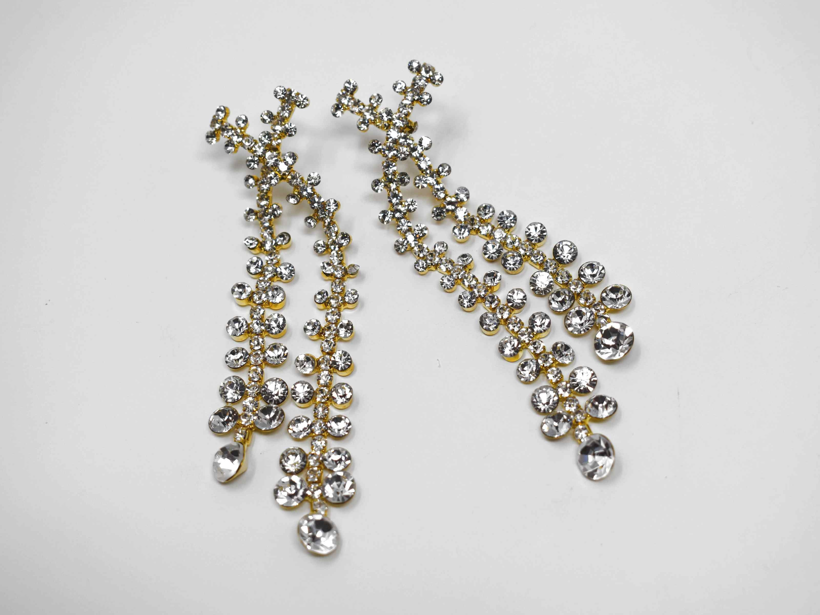 Detailed and distinctive our gypsop formal drop dangle statement earrings are gold with a cluster of clear stones.These earrings are 3 1/2 inches in length with a push back clasp.