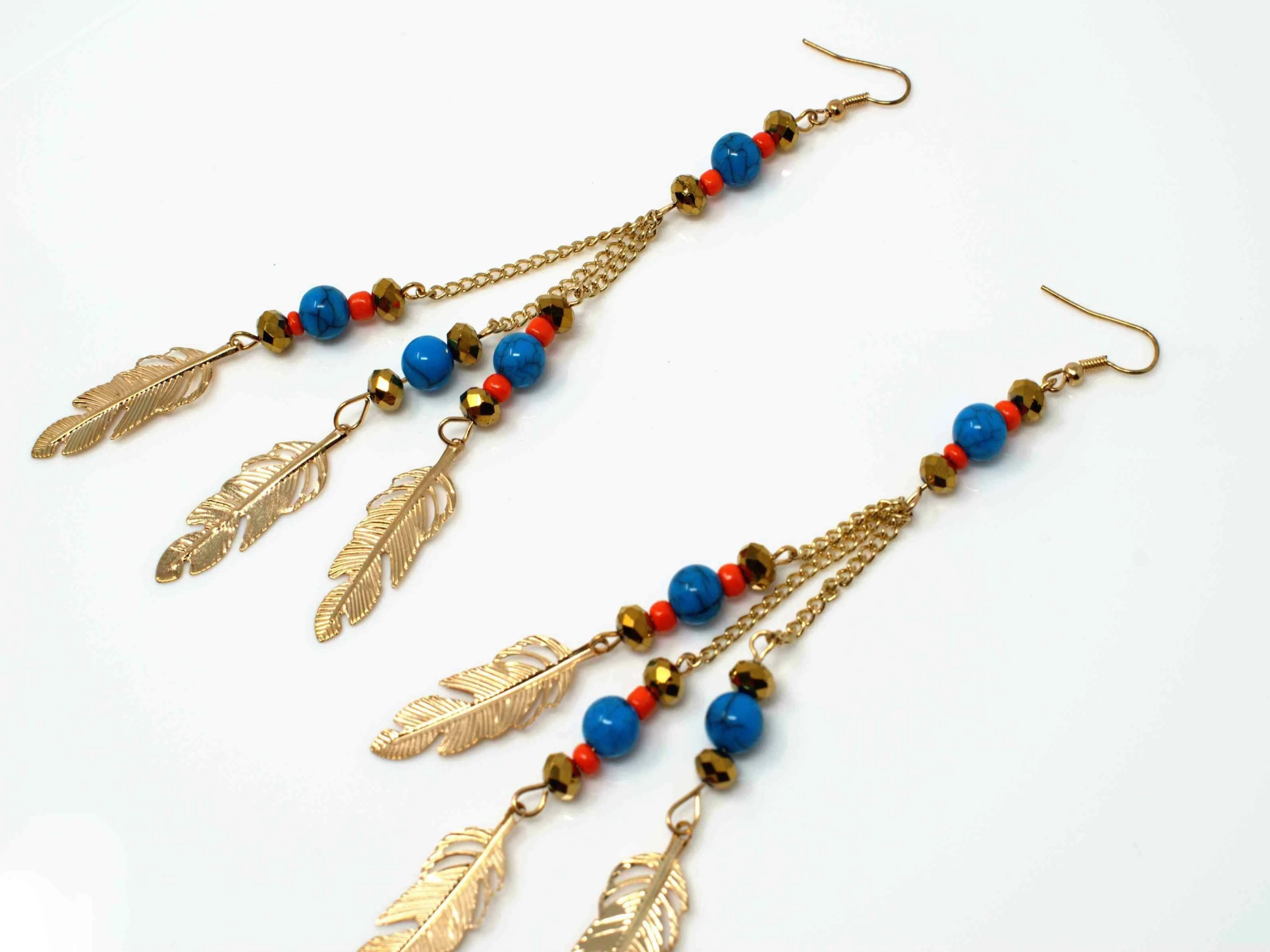 A charming gold drop dangle earring accented with bead and feather charms and a fish hook clasp.