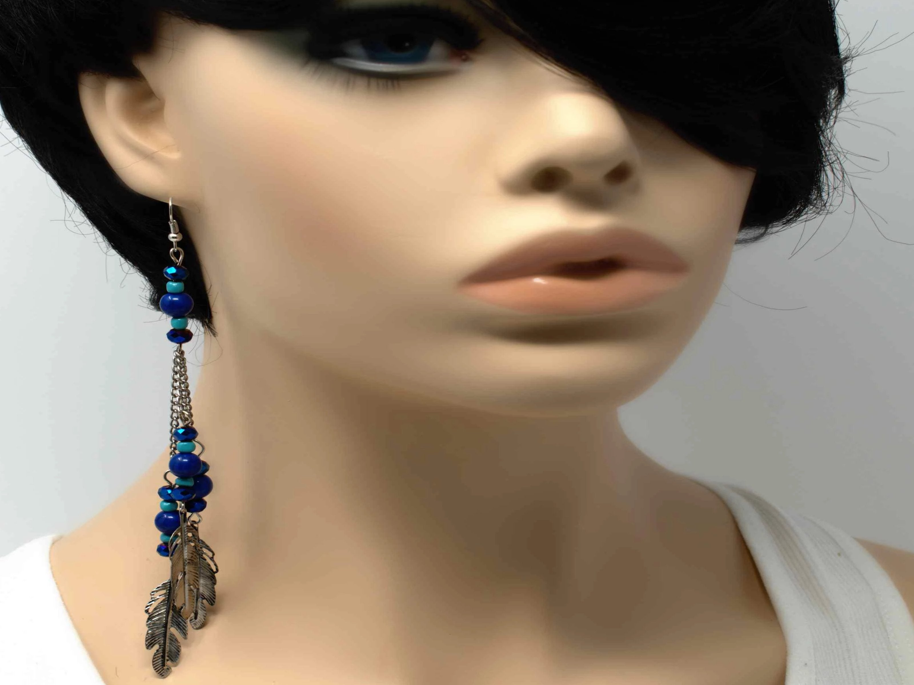 A charming silver drop dangle earring accented with bead and feather charms and a fish hook clasp.