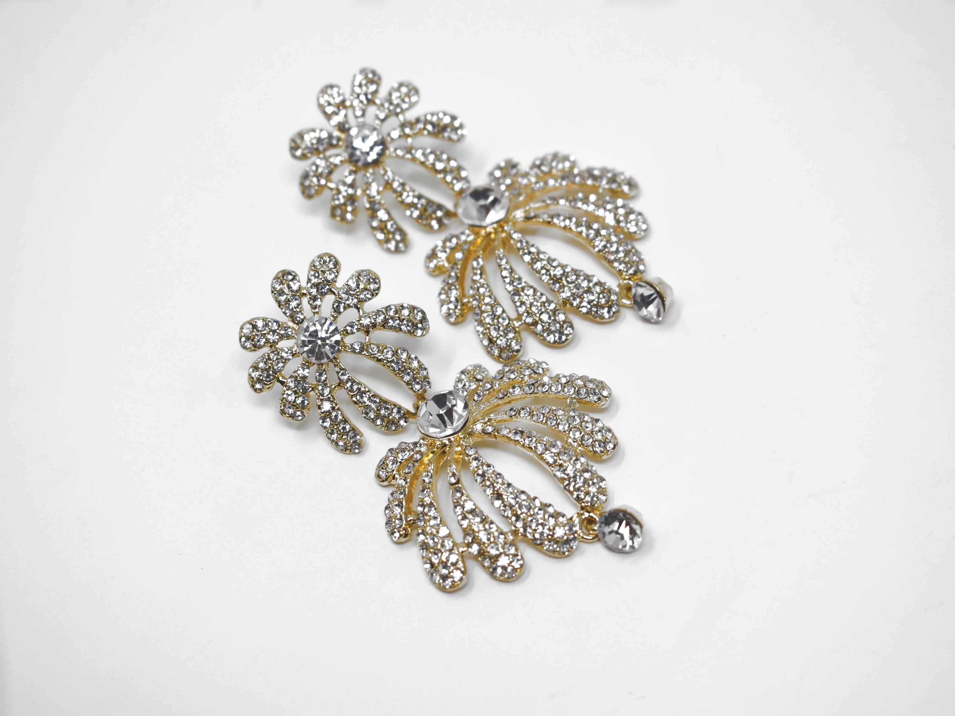 A radiant burst of sparkle is how you would describe our helenium gold earrings. These are a two tier floral burst formal drop earring with clear stones. They are 2 1/2 inches in length with a pushback clasp.