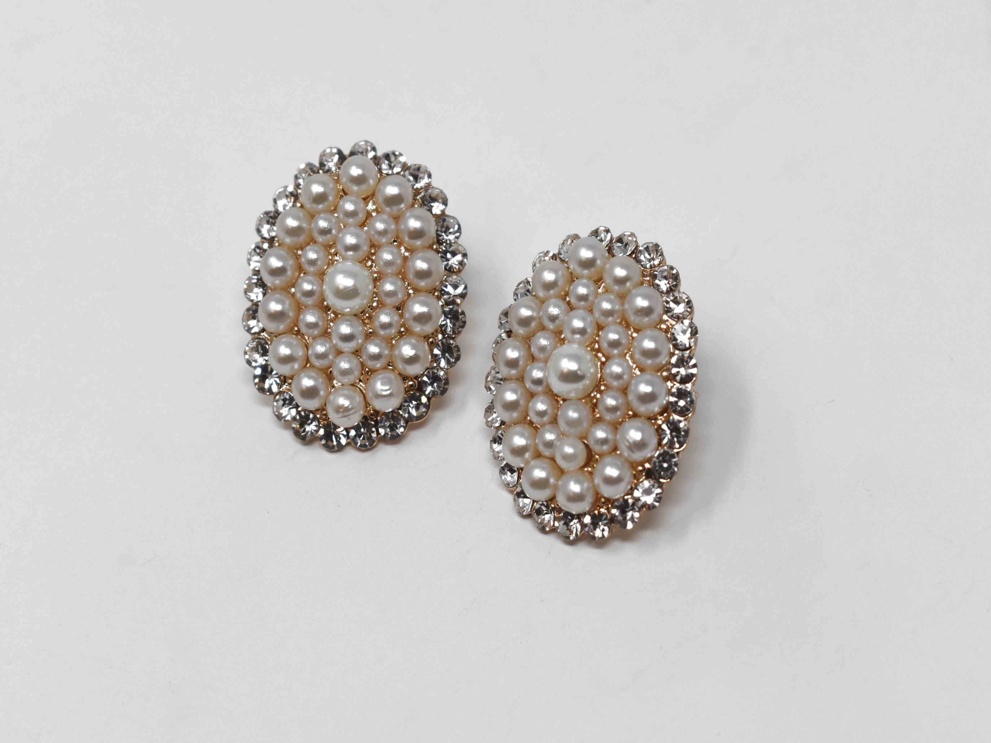 Our adorable Hosta knob earrings is the perfect addition to your wardrobe. Its oval shape is covered in pearl clusters and and has a gold tone with a push back clasp.