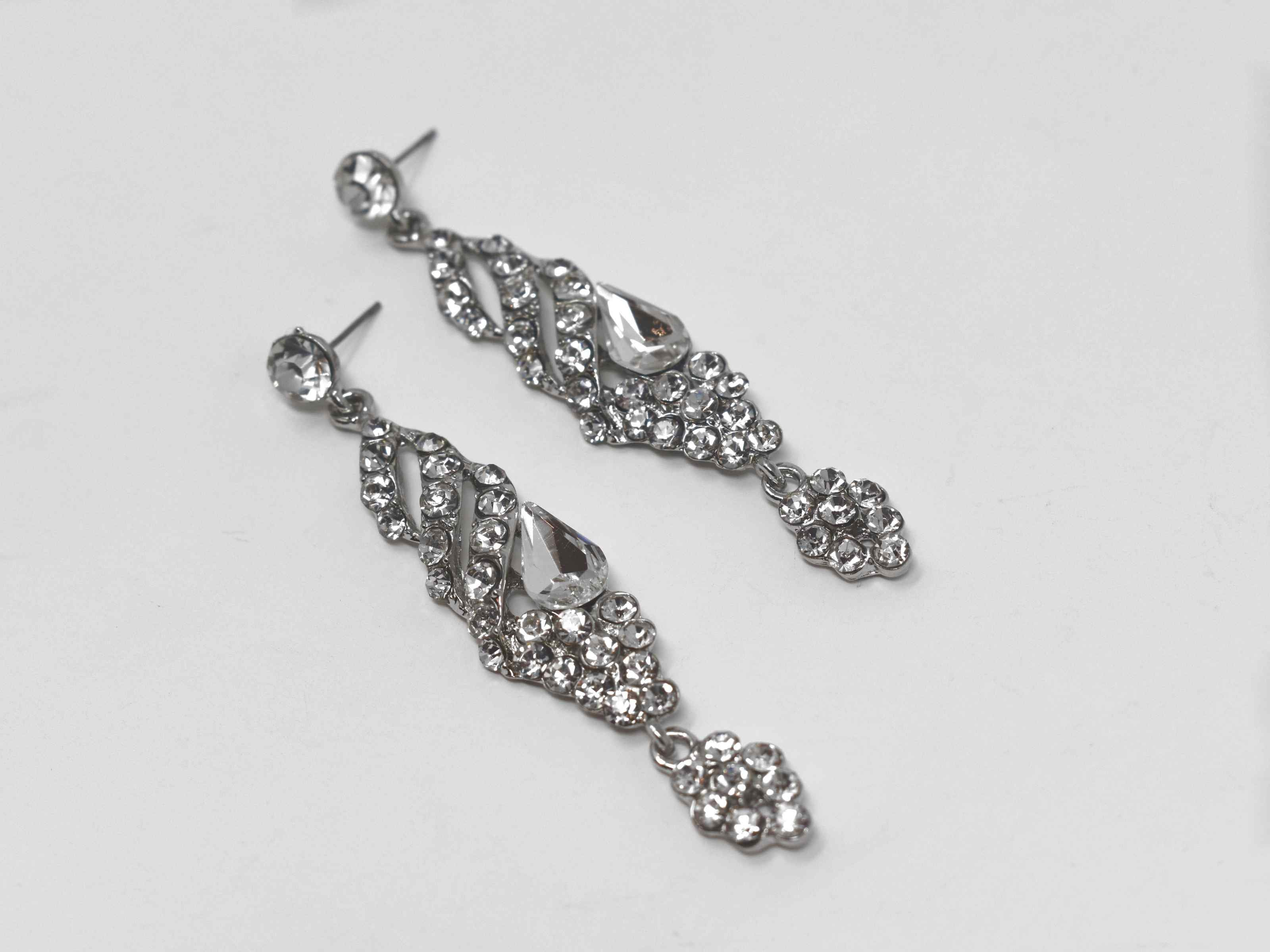 These formal silver earrings are a classic addition to your outfits. They are 3 inches in length and encrusted with clear stones.