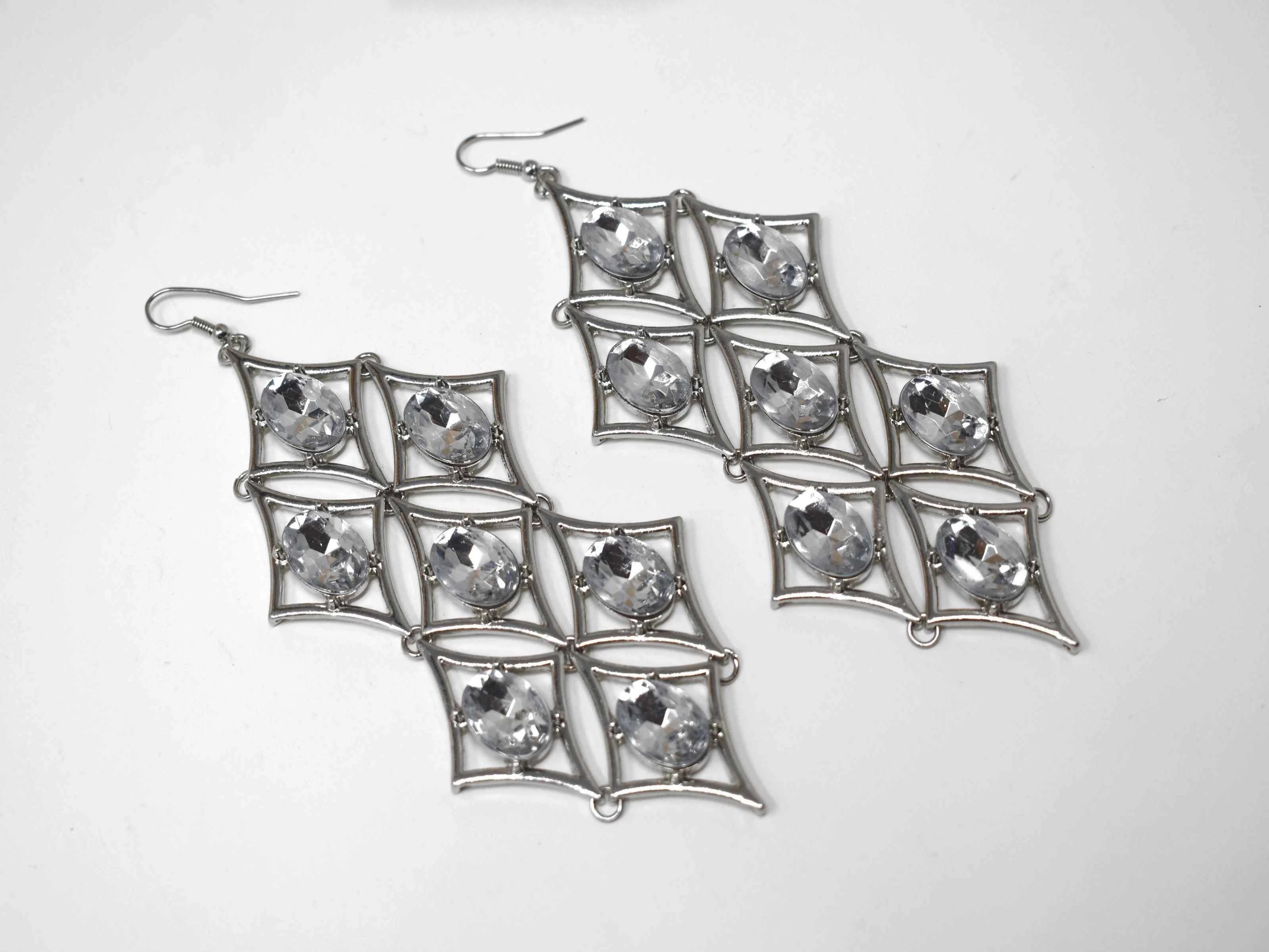 Let our Iris chandelier Silver earrings add a gorgeous glow to any outfit. These chandelier earrings has a diamond shape accented with clear stones. It has fishhook clasp and is about 5 inches in length.