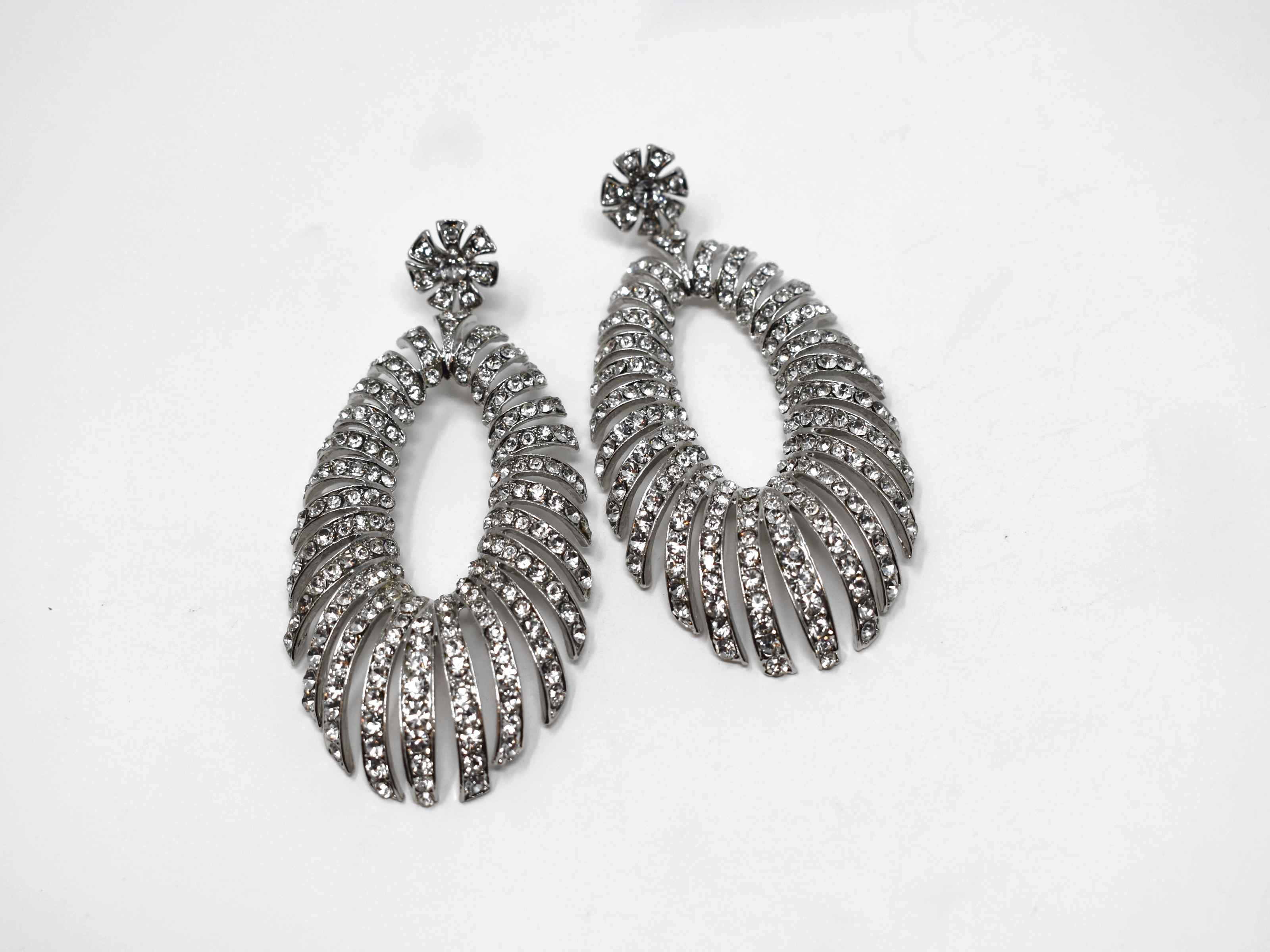 A timeless treasure! These Jamesia silver formal statement earrings have a unique oval shape. These drop earrings are 3 inches in length with a push back clasp.
