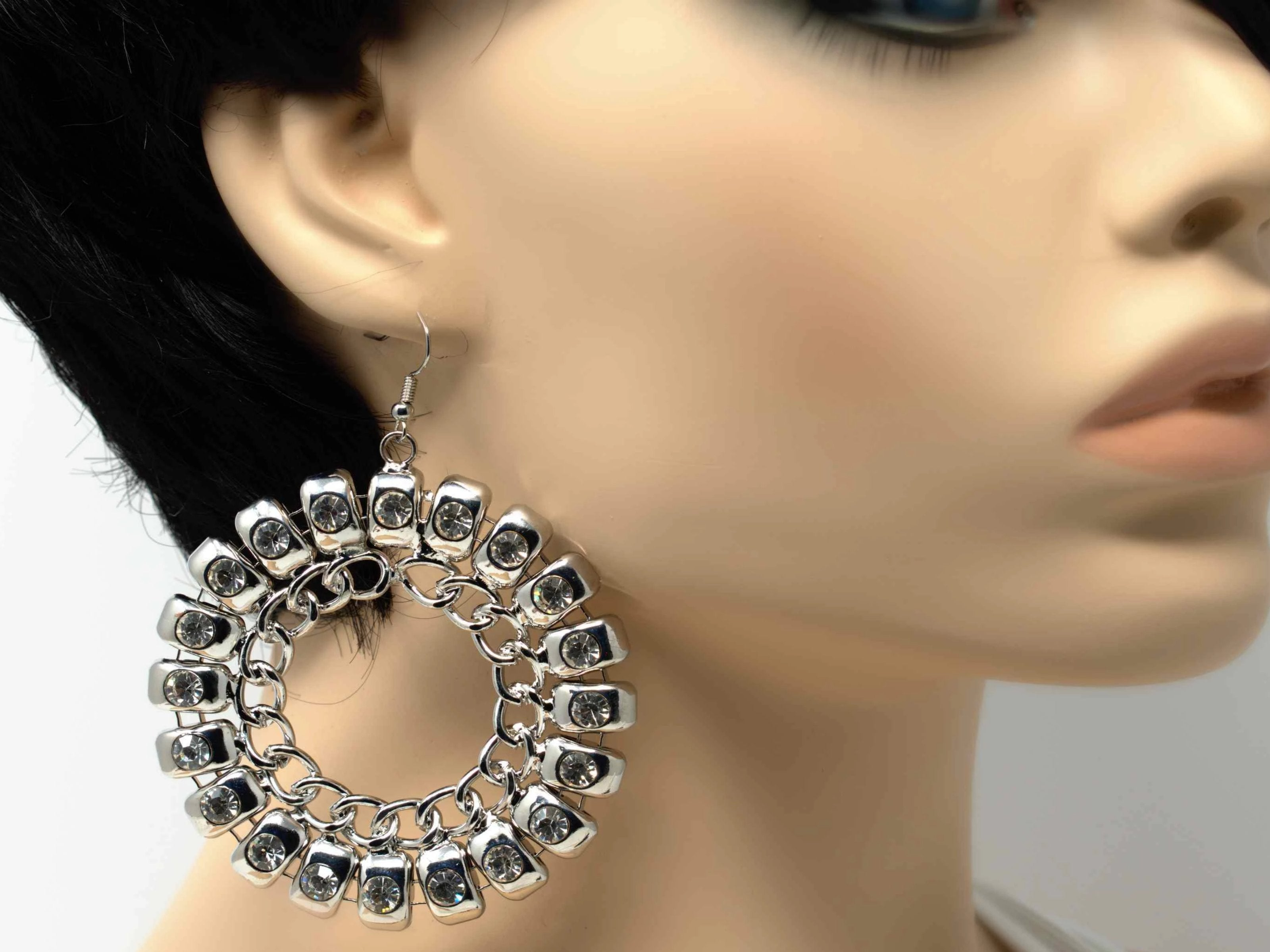 An exquisite silver dangle drop fashion earring with stones and chain accent and a fish hook clasp.
