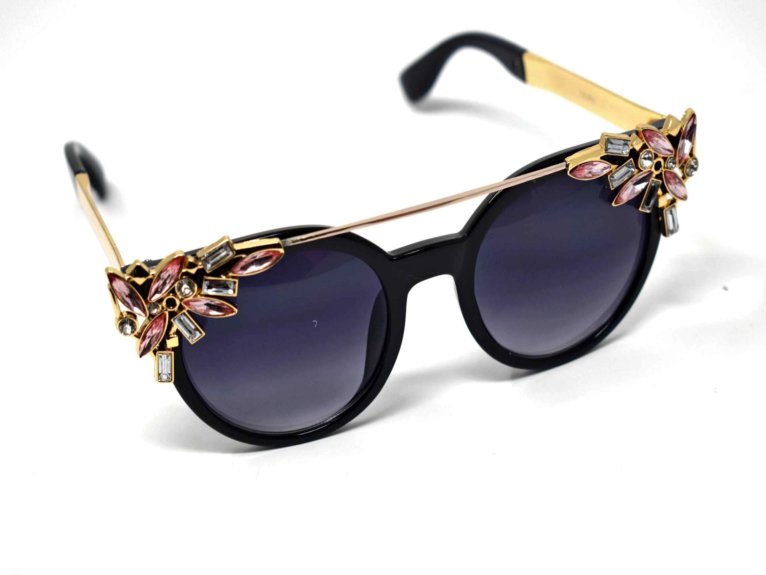 Trend setter and attention getter is what they will call you in these Pansy black sunglasses with a sleek gold trim adorned in pink and clear gems, in a pantos style frame.