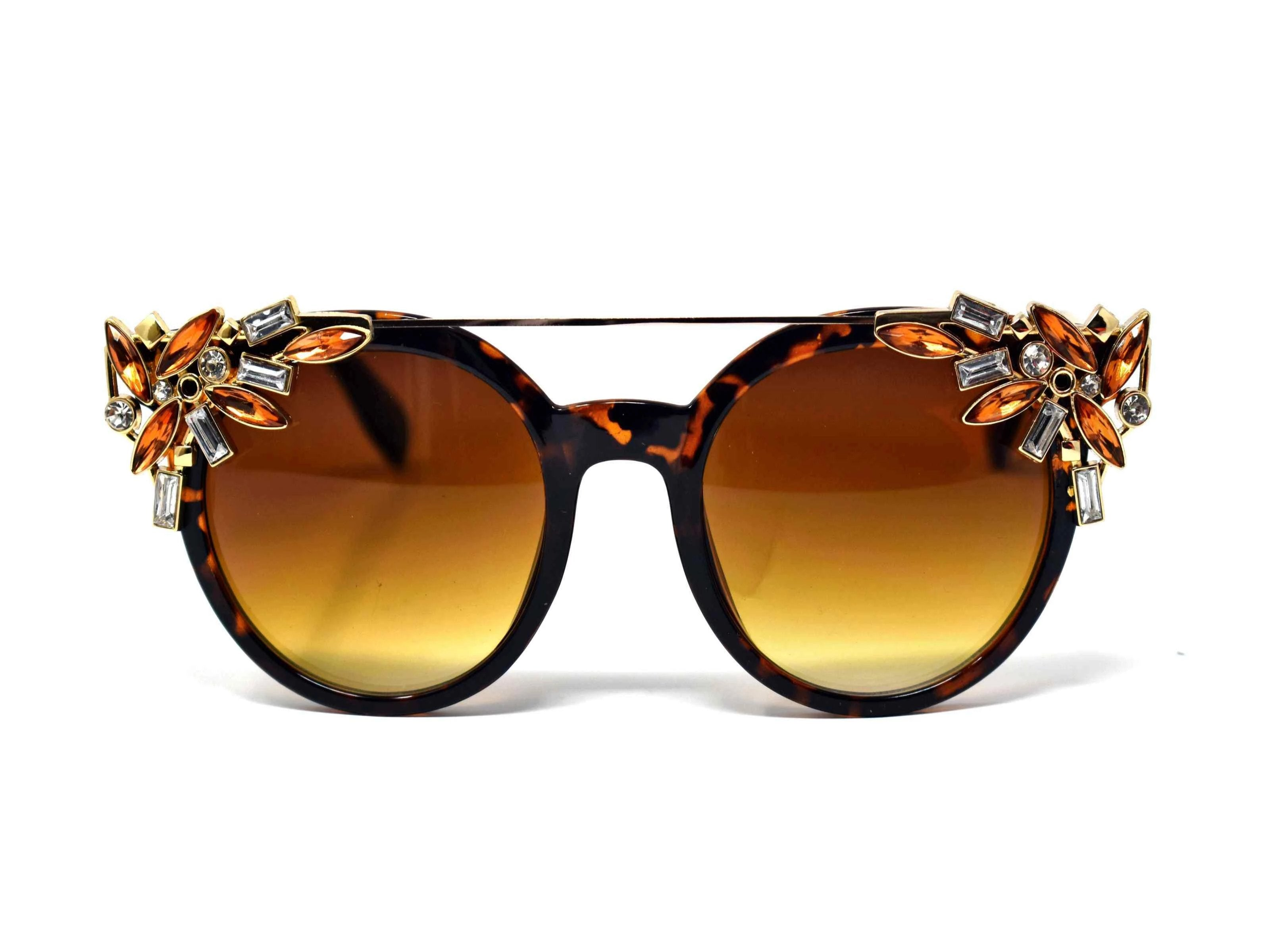 Trend setter and attention getter is what they will call you in these Pansy Leopard sunglasses with a sleek gold trim adorned in clear and brown gems, in a pantos style frame.