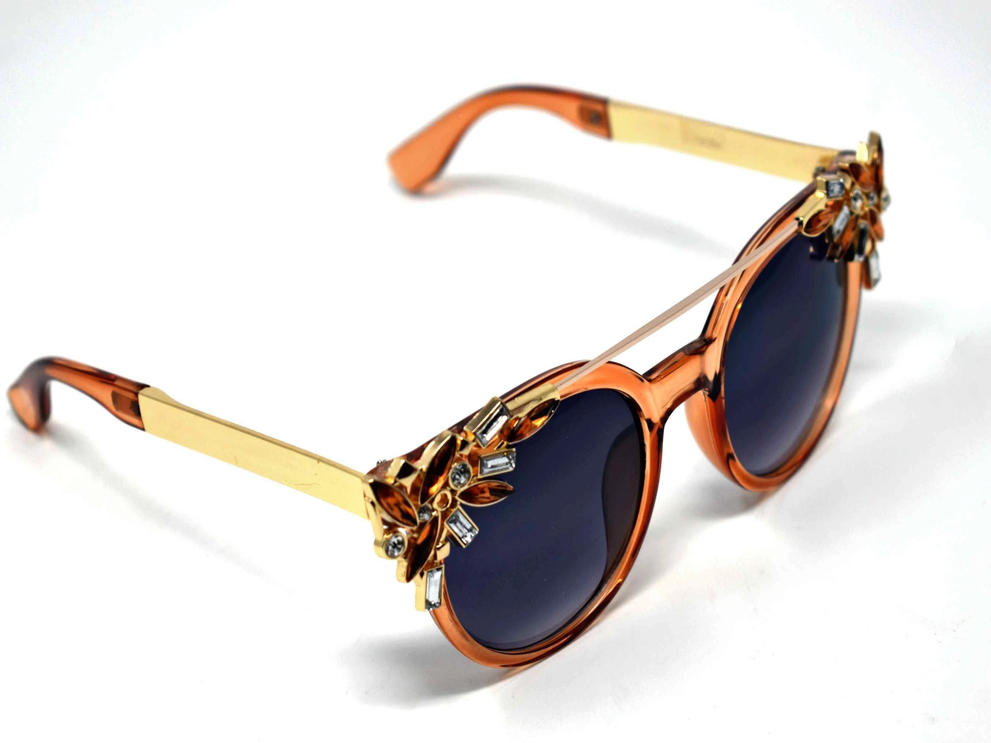 Trend setter and attention getter is what they will call you in these Pansy brown sunglasses with a sleek gold trim adorned in brown and clear gems, in a pantos style frame.