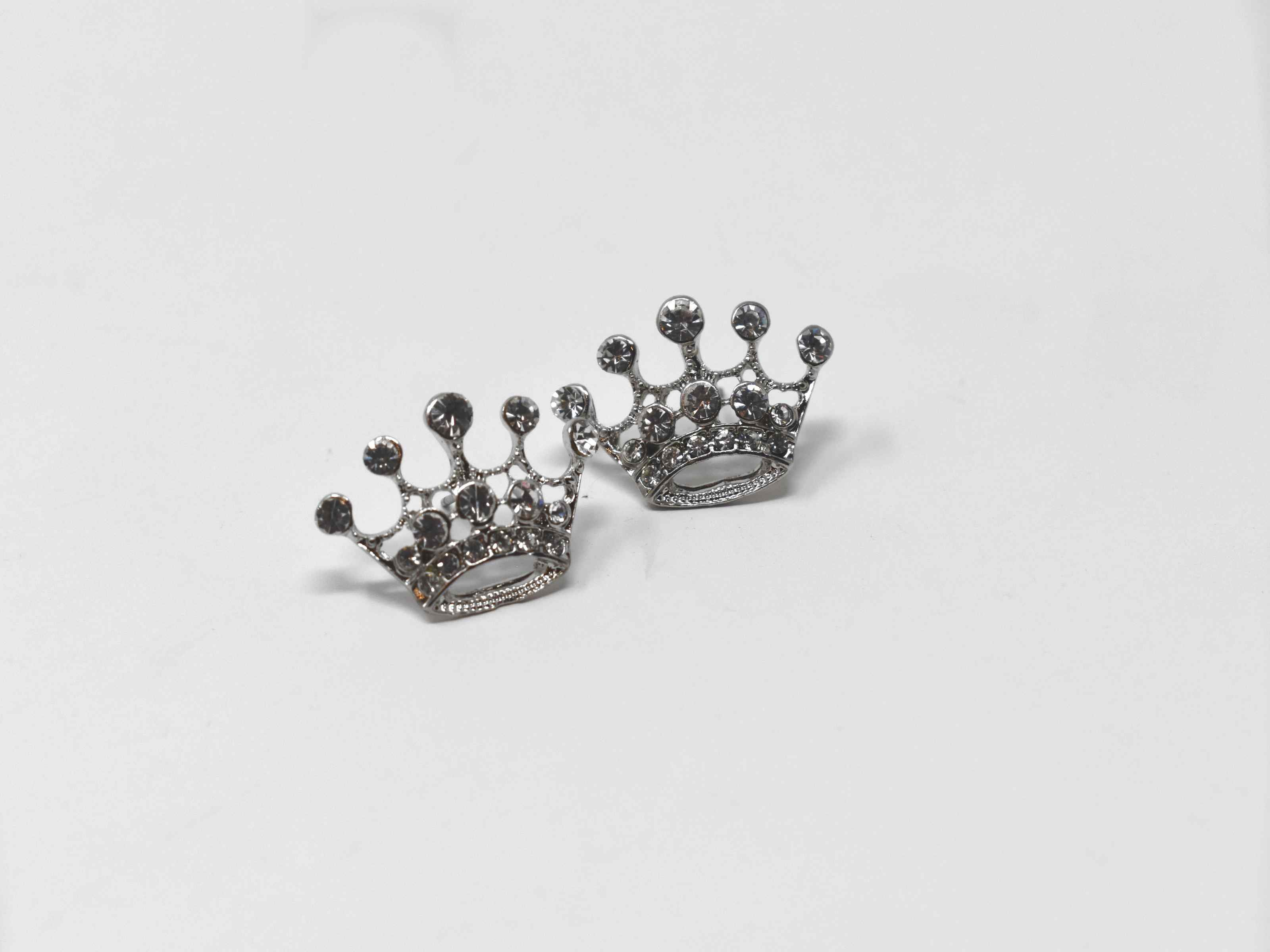 Let our queens cup be your new essential go to staple. These silver knob crown shaped earrings are encrusted with stones, 1/2 an inch in length with a pushback clasp.