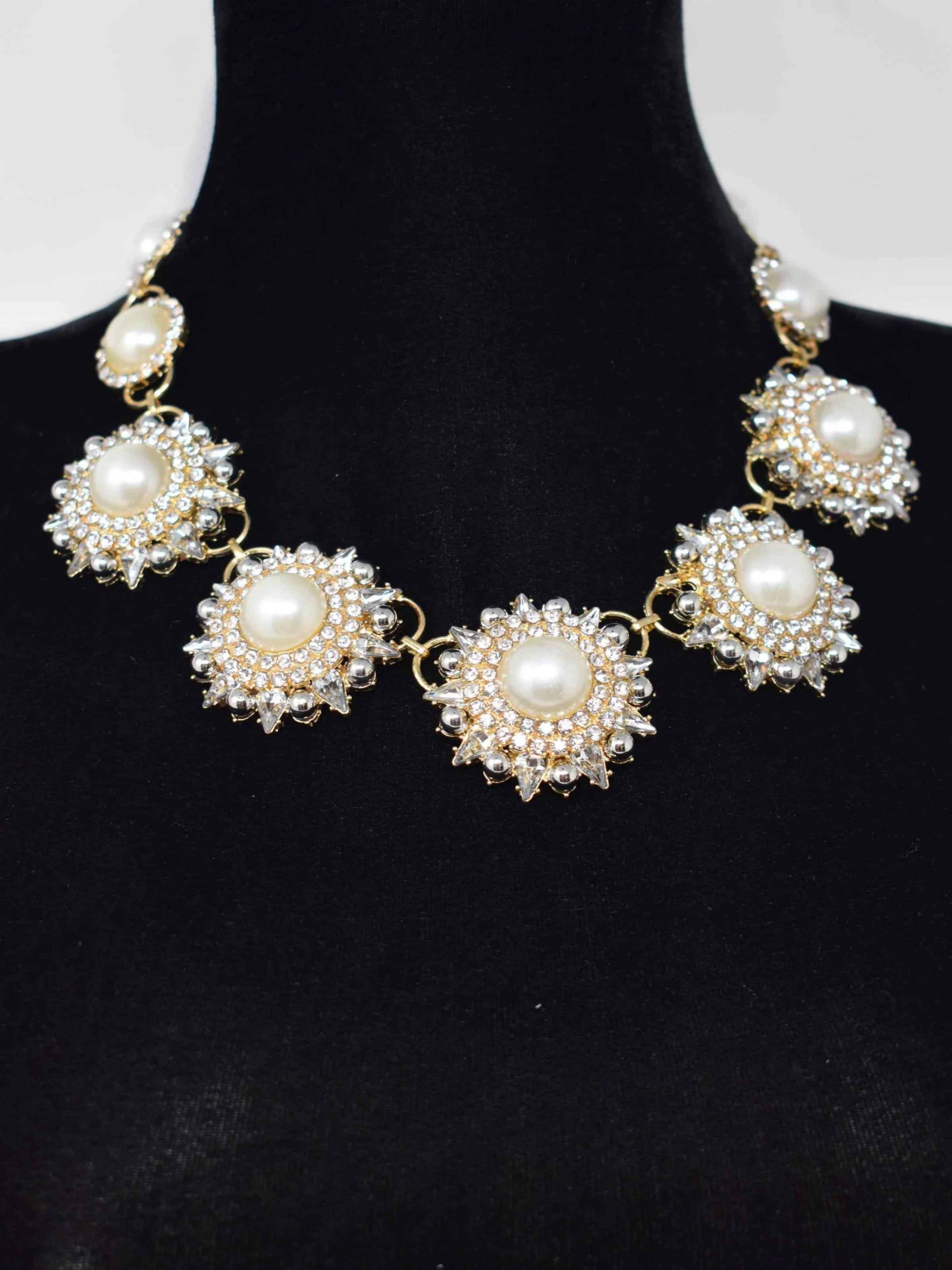 "Our Rica statement necklace will add an elegant stylish glow to your outfit. This Gold and pearl floral linked necklace is accented with stones and closes with a lobster clasp. It measures 10 1/2"" in length."