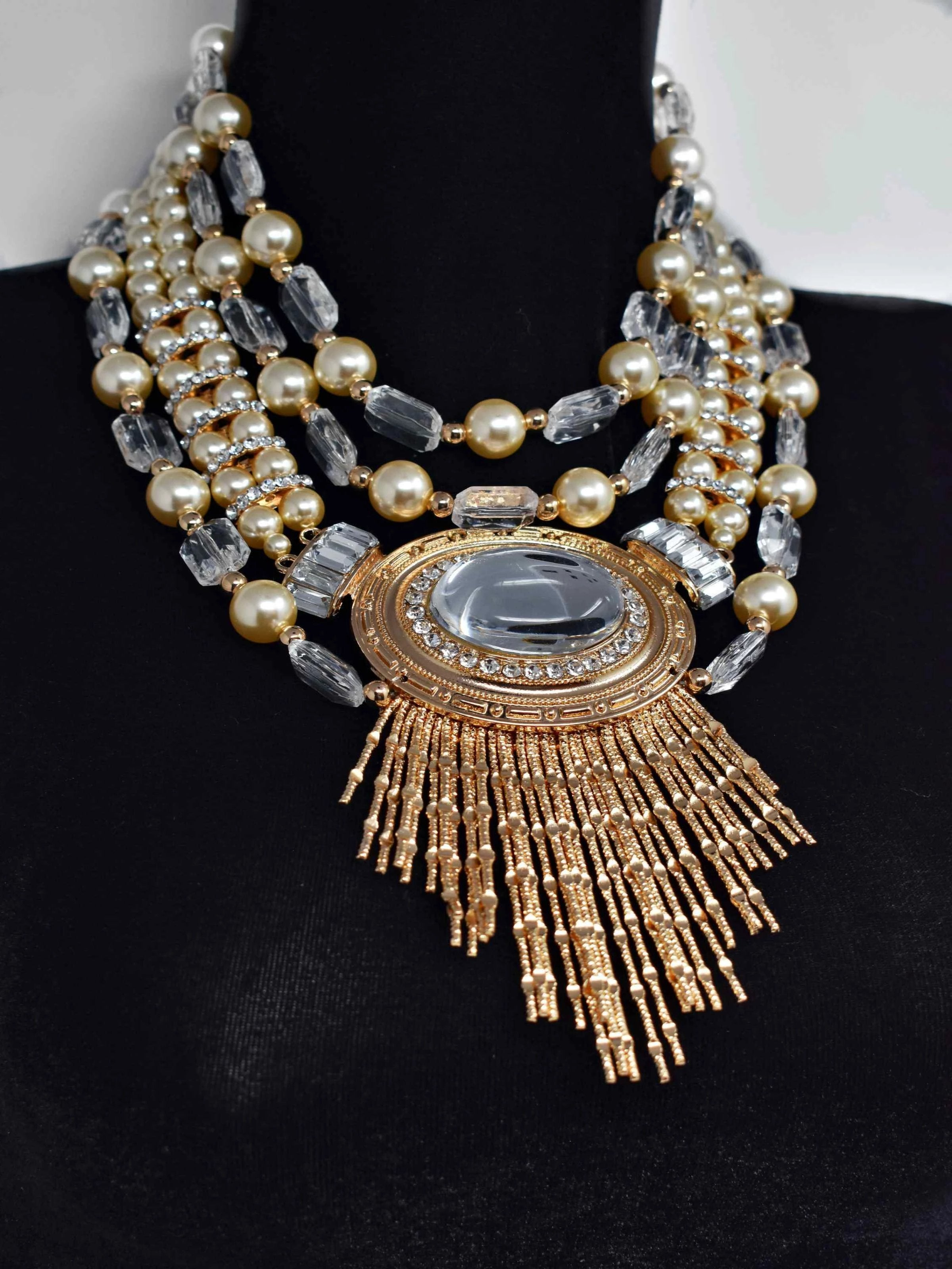 "Our Rium gold and pearl necklace makes a standout addition to your collection.  This multi strand statement necklace is 17"" in length with a lobster claw clasp."