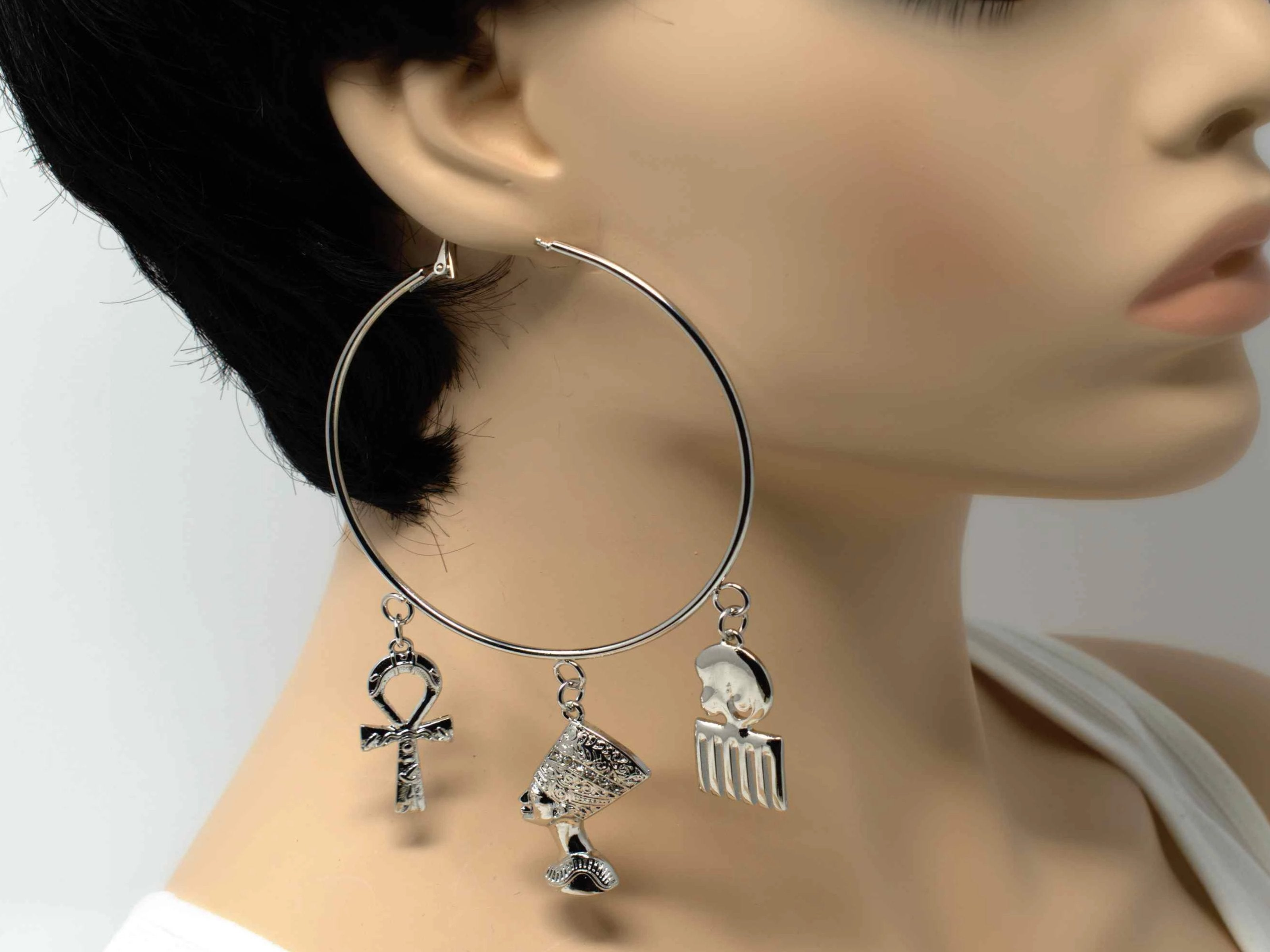 A radiant stylish afro chic silver hoop fashion earring with afro centric charms.