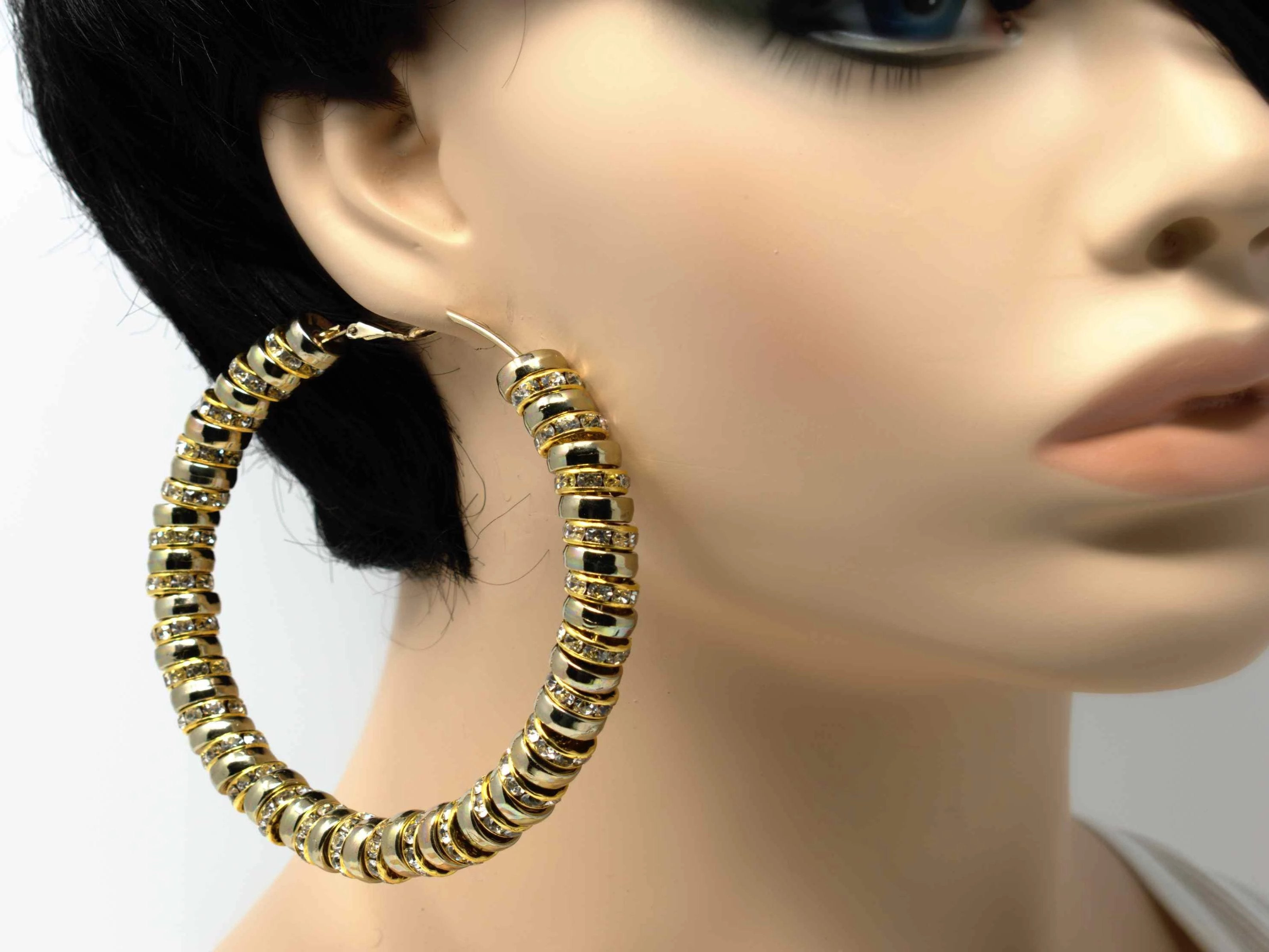 A gold hoop multi charmed earring which gives an elegant twist to an original staple.