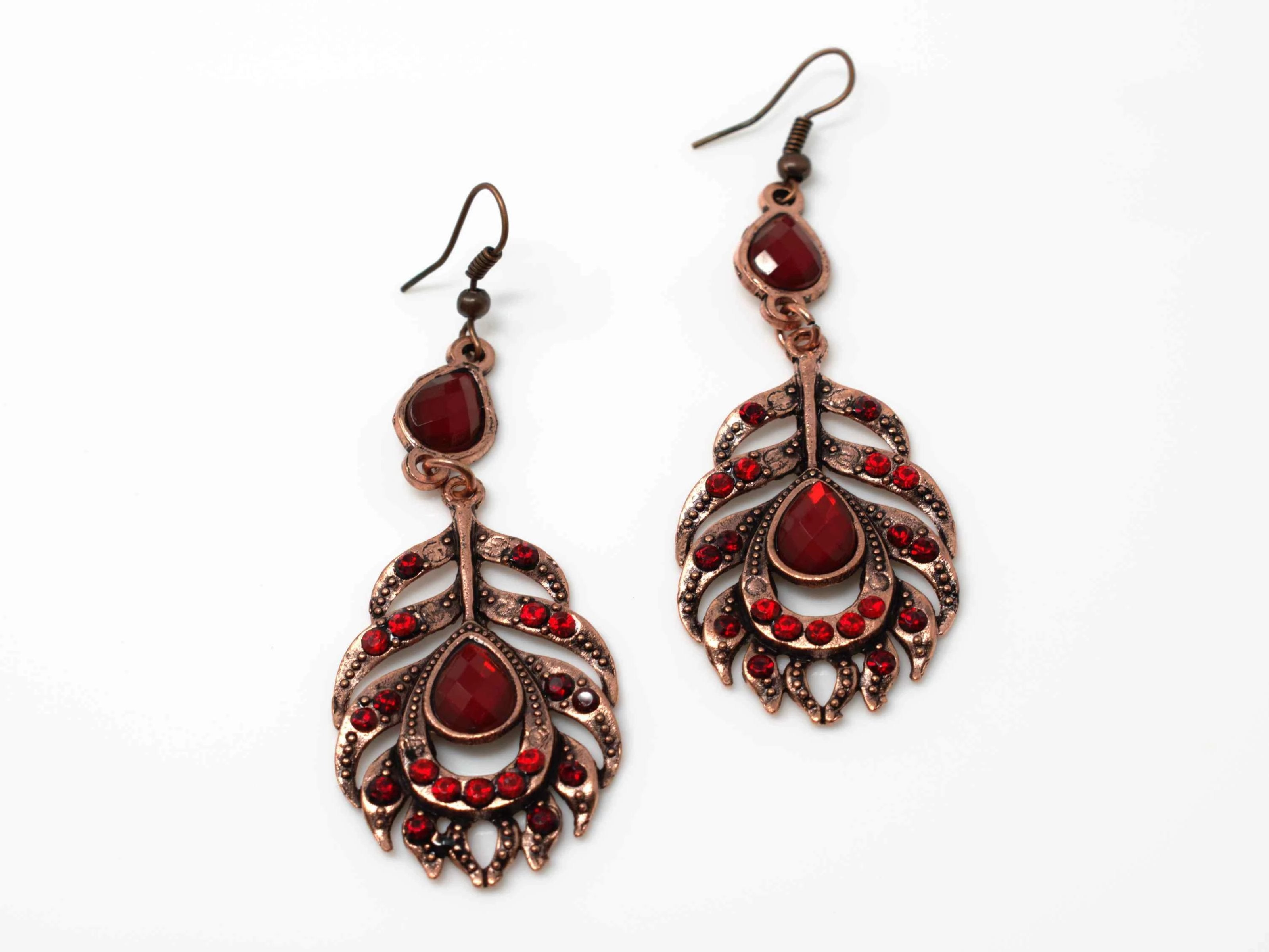 A dainty rose drop dangle feather fashion earring with red accent stones and a fish hook clasp.