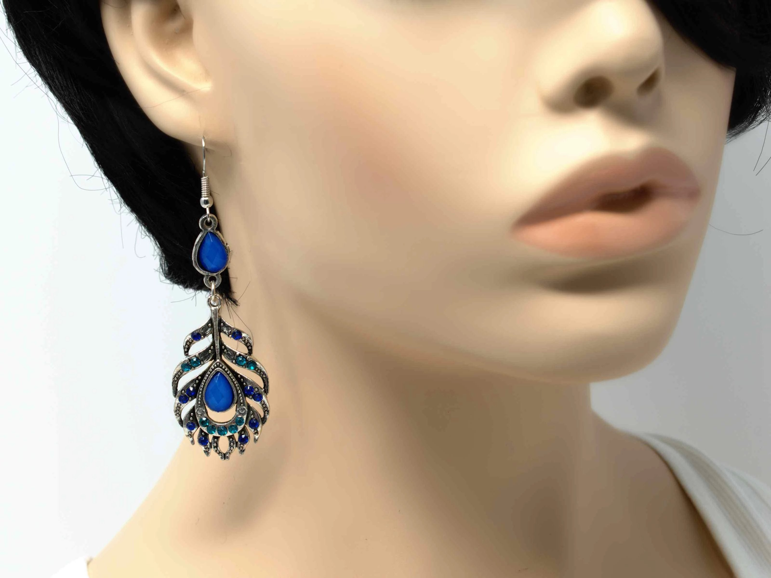 A dainty silver drop dangle feather fashion earring with blue accent stones and a fish hook clasp.