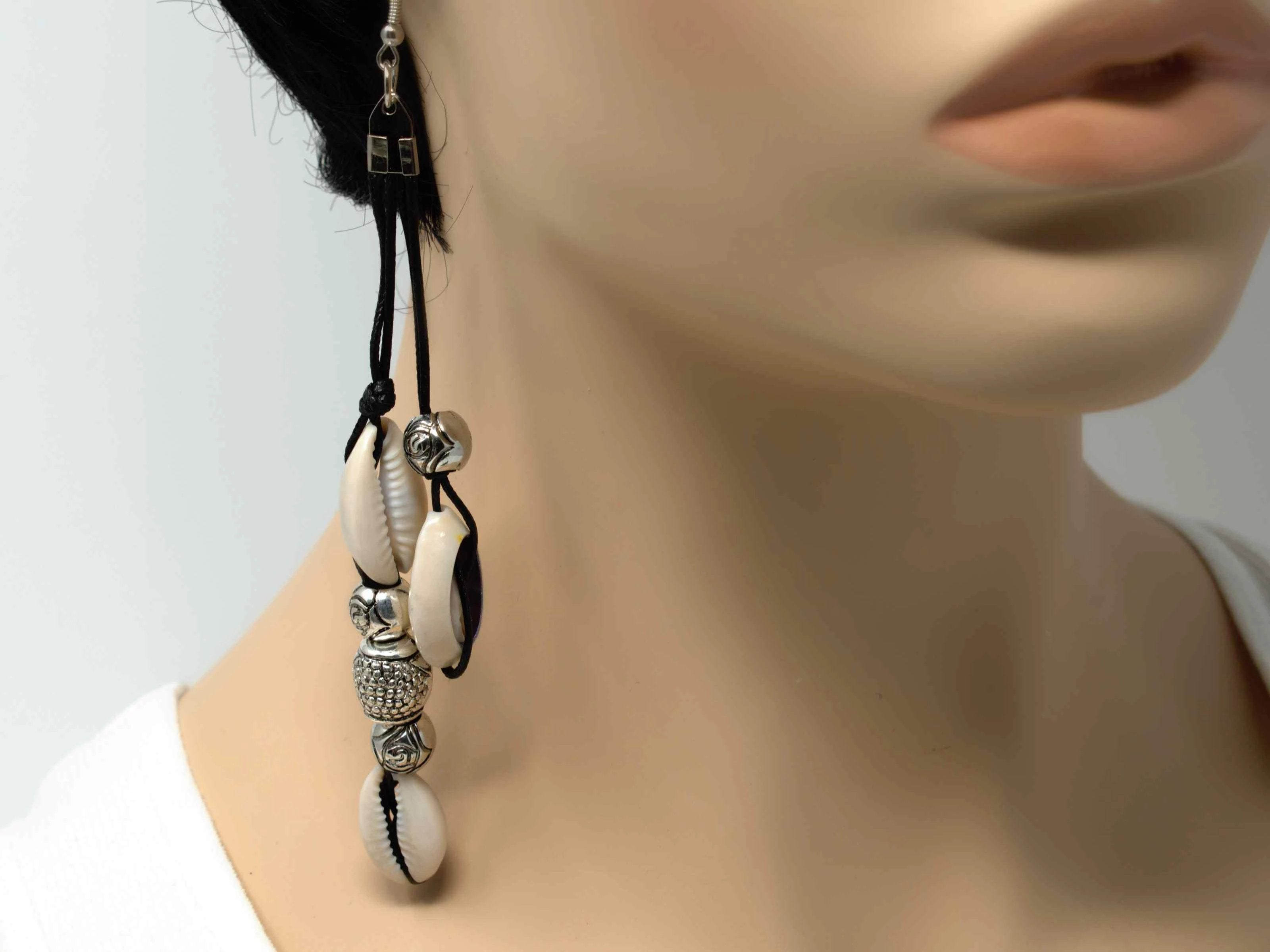 An artisan style black dangle rope fashion earring with shells and silver beads. Comes with a fish hook clasp.