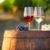 Red & White Wine in Glasses on top of a Barrel with Grapes & Cheese