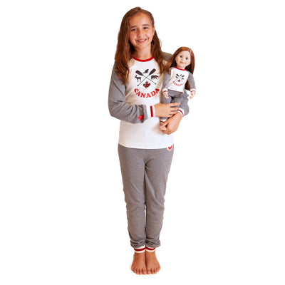 Girl wearing Canadian pajamas that match her 18 inch doll pjs.