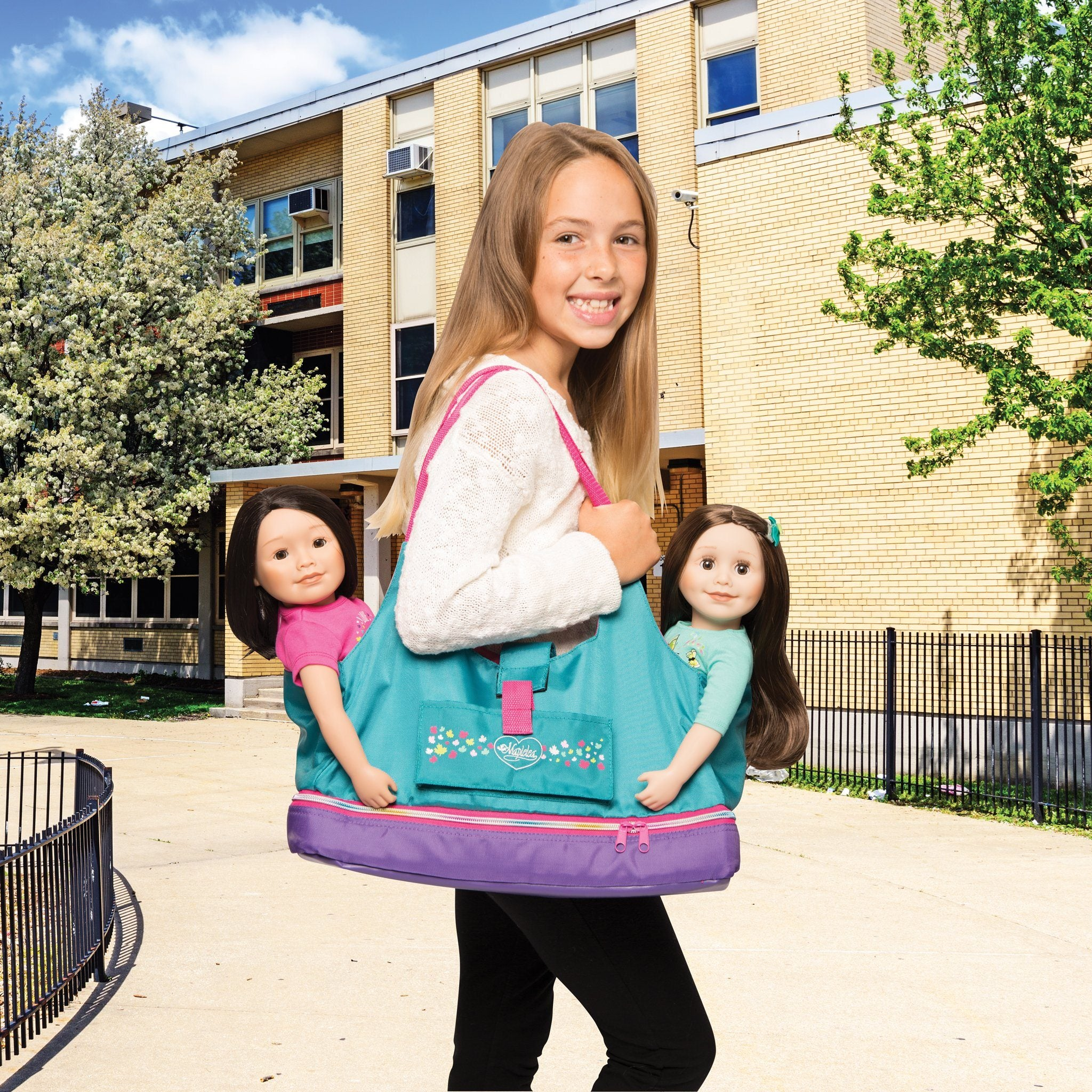 Girl with Maplelea Doll Tote in teal, pink and purple carries two dolls.