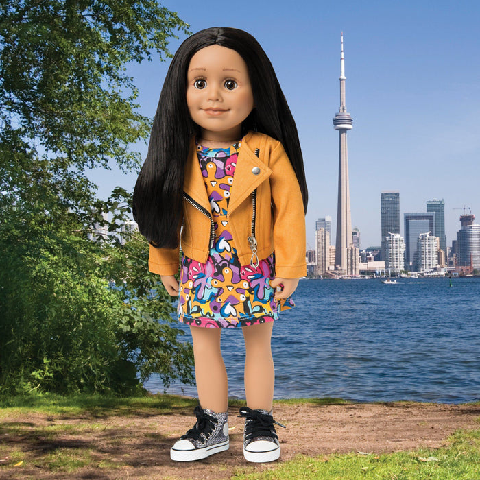 Maplelea doll Alexi wearing orange moto jacket, print dress and metallic runners on a Toronto background