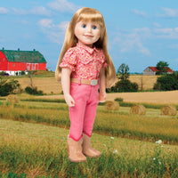 Maplelea 18 inch doll Brianne with story journal wearing pink patterned button-up shirt, pink pants, beige belt with sparkly buckle and beige riding boots. Shown in a Manitoba farm field.