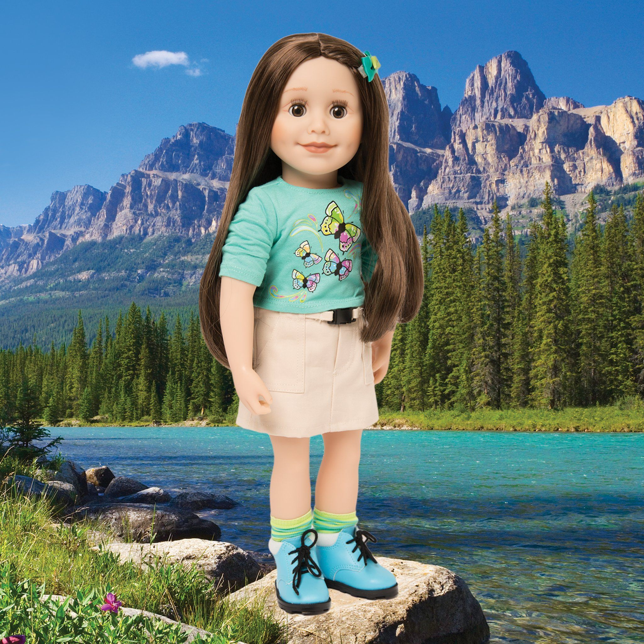 Maplelea 18 inch doll Taryn wearing green butterfly graphic t-shirt, khaki skirt, striped socks and blue hiking boots. Comes with story journal and storage box.
