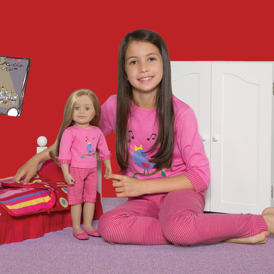 A girl wearing pink Nightingale Nightwear pajamas holding an 18 inch doll with matching PJs.