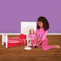 Girl playing with 18 inch doll and doll furniture including deluxe wardrobe.